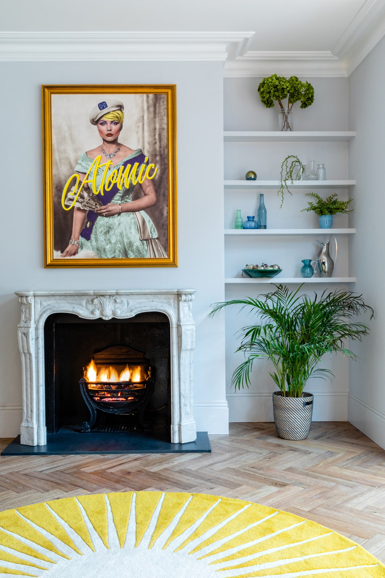 Detail interior photo: sitting room with light blue walls; picture above a fire place with Debbie Harry with a sign