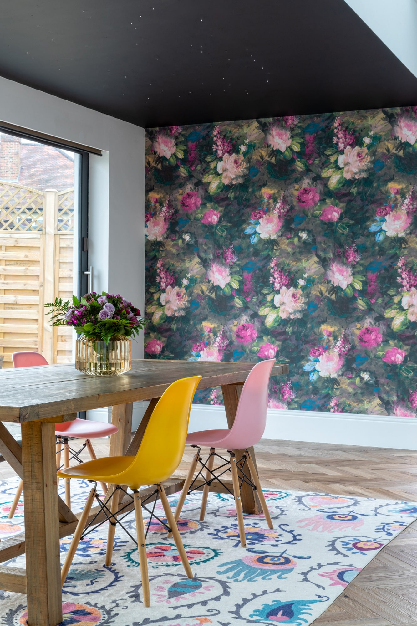 Interior design photo: dining area with floral wallpaper, wooden table, plastic yellow and pink chairs; black ceiling