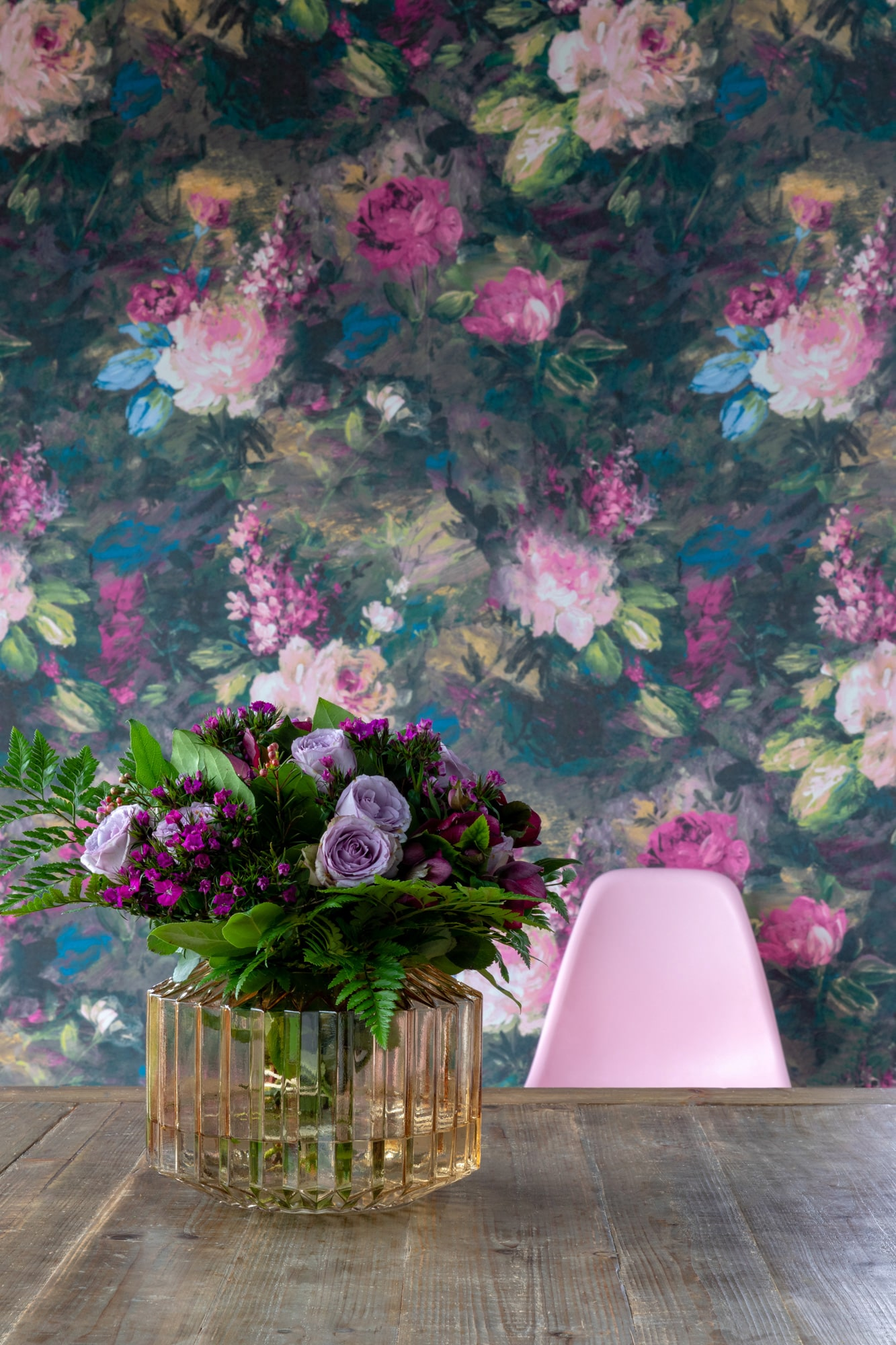 interior detail photo of a vase with flowers, floral wallpaper on the background and a pink chair