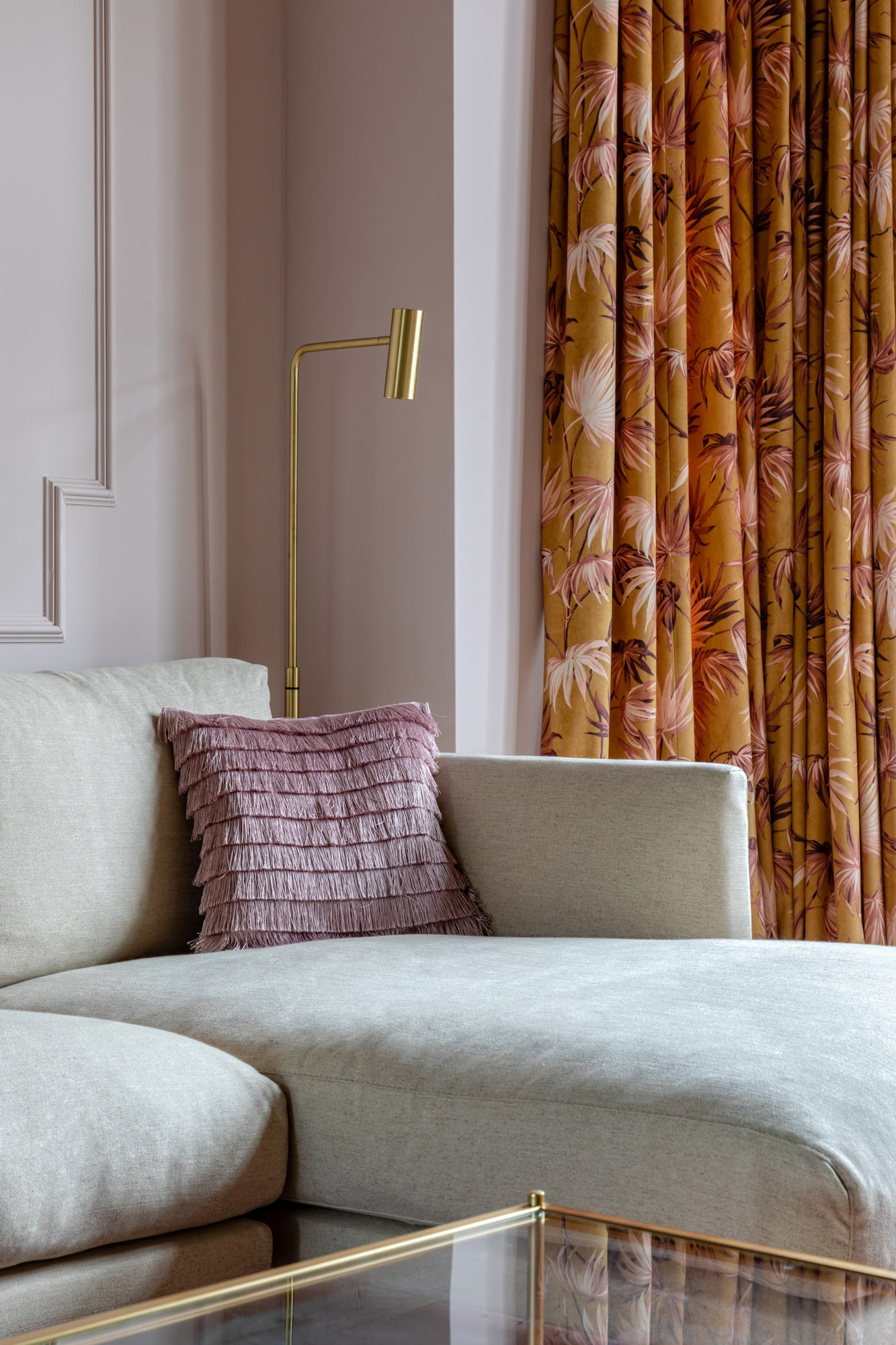 Interior design shot: beige sofa; pink cushion with tassels; floral print on curtains