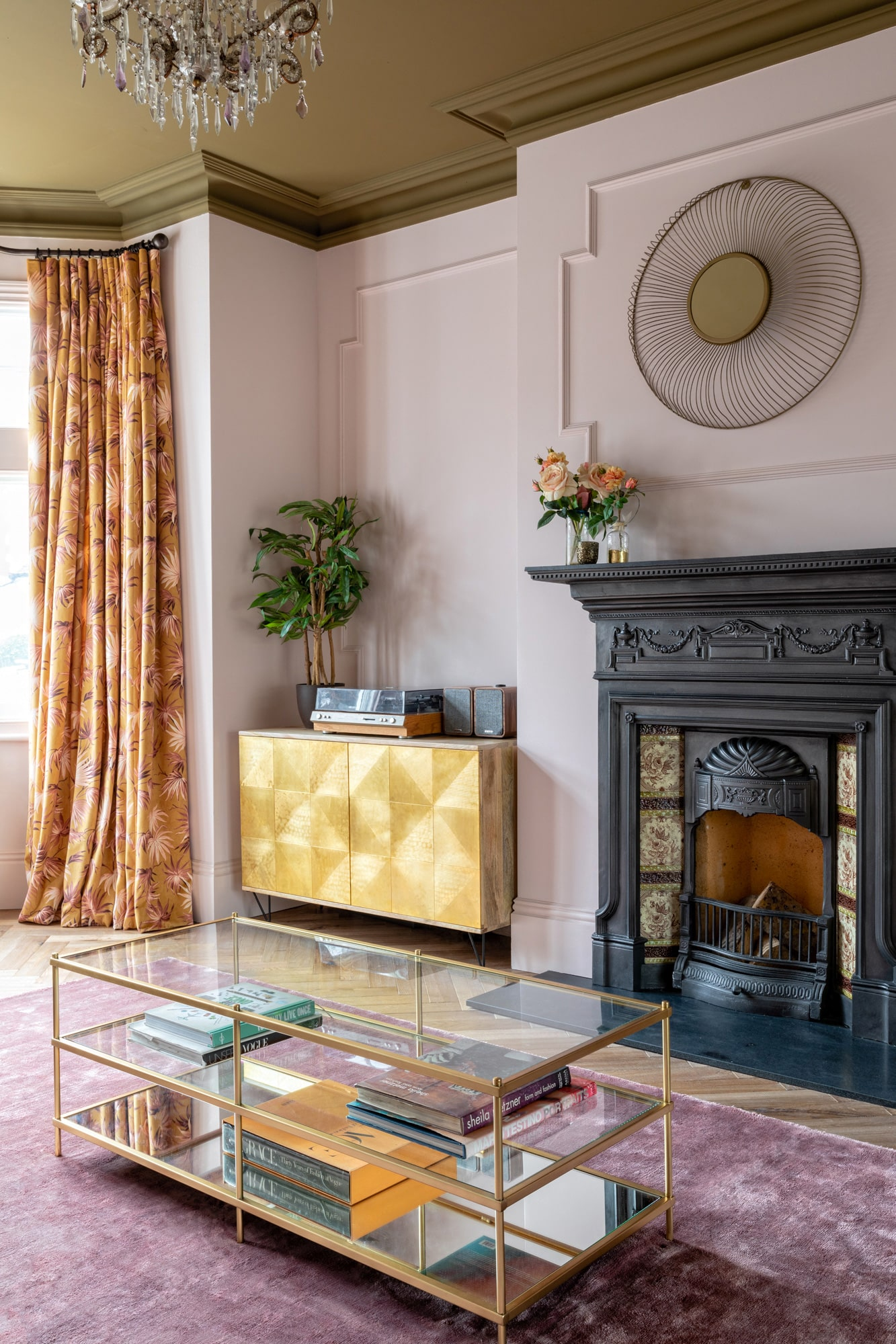 Interior photo: living room with light pink walls and olive ceiling; fireplace with logs; glass and gold metal coffee table; floral print on curtains; golden cabinet in the corner