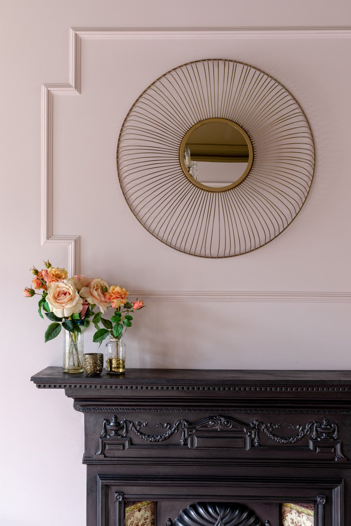 Interior detail shot: pink walls, a vase above a fireplace; round mirror