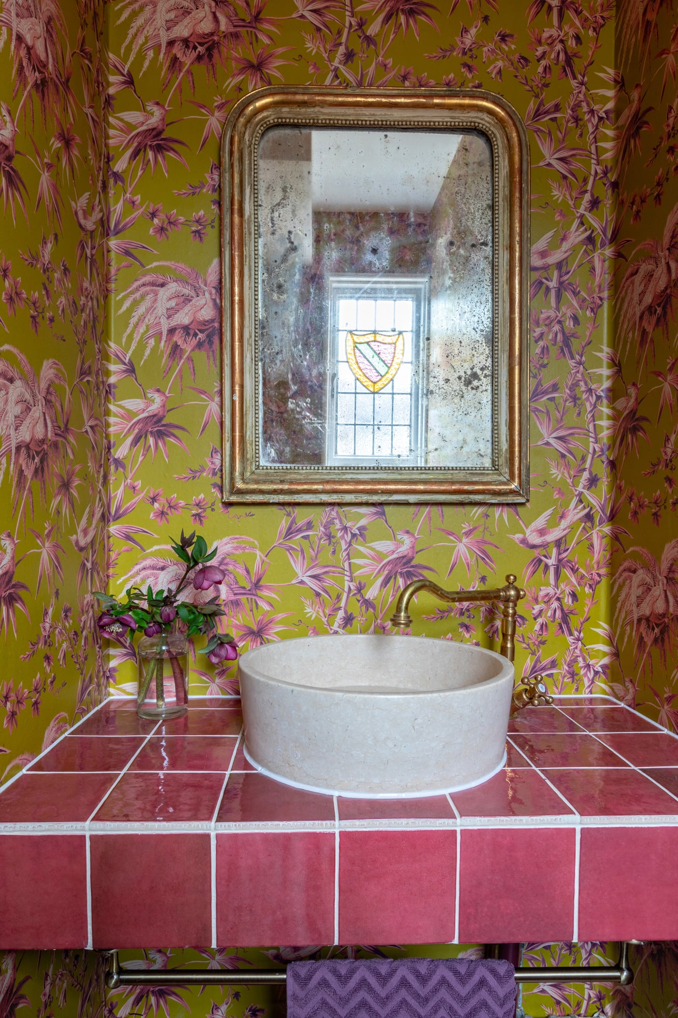 Interior shot: cloakroom with colourful floral wallpaper, sink with brass tap, a glass with purple flowers