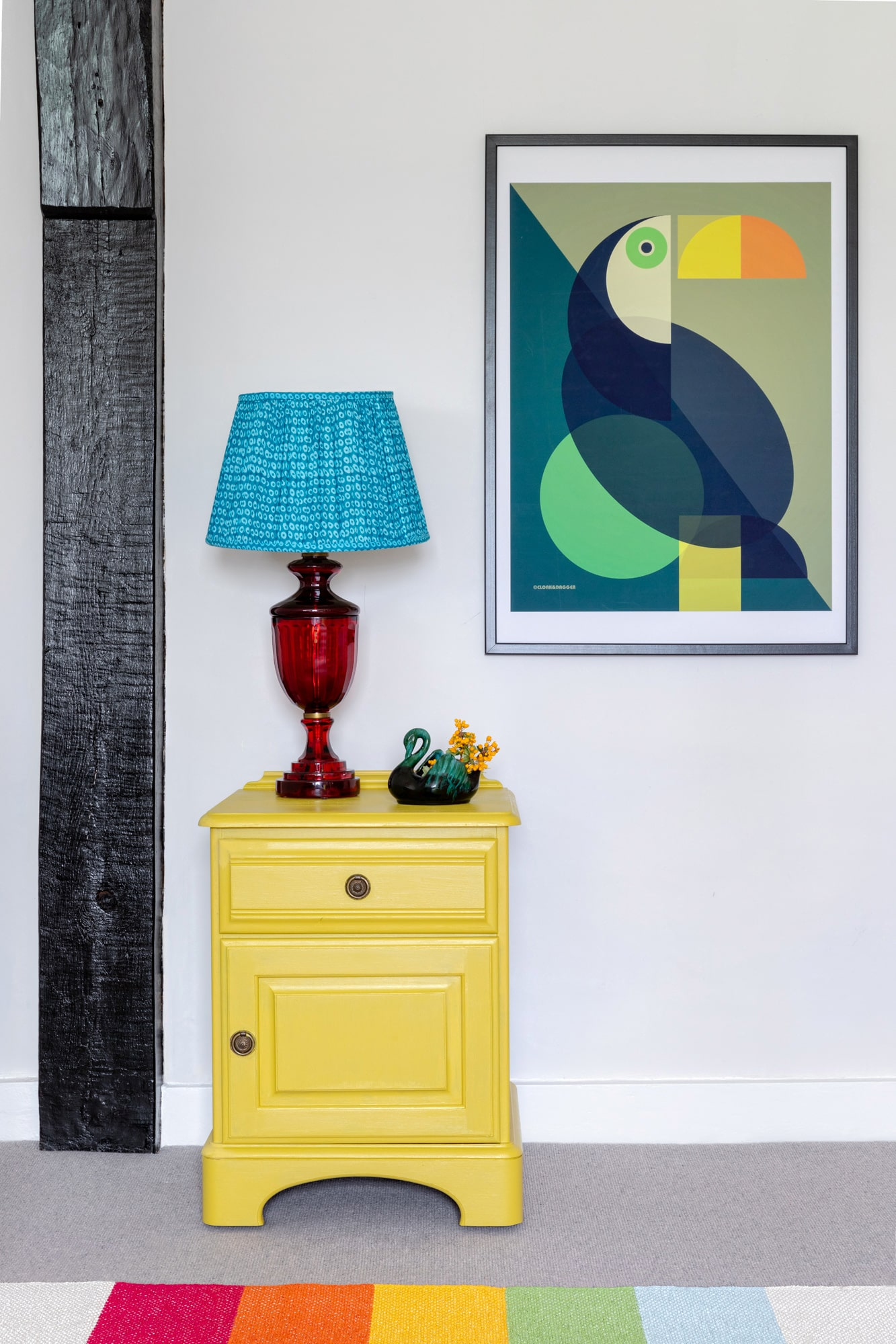 detail interior shot of a bedroom: yellow bedside table with red and blue lamp; vivid poster of a toucan bird on the wall above