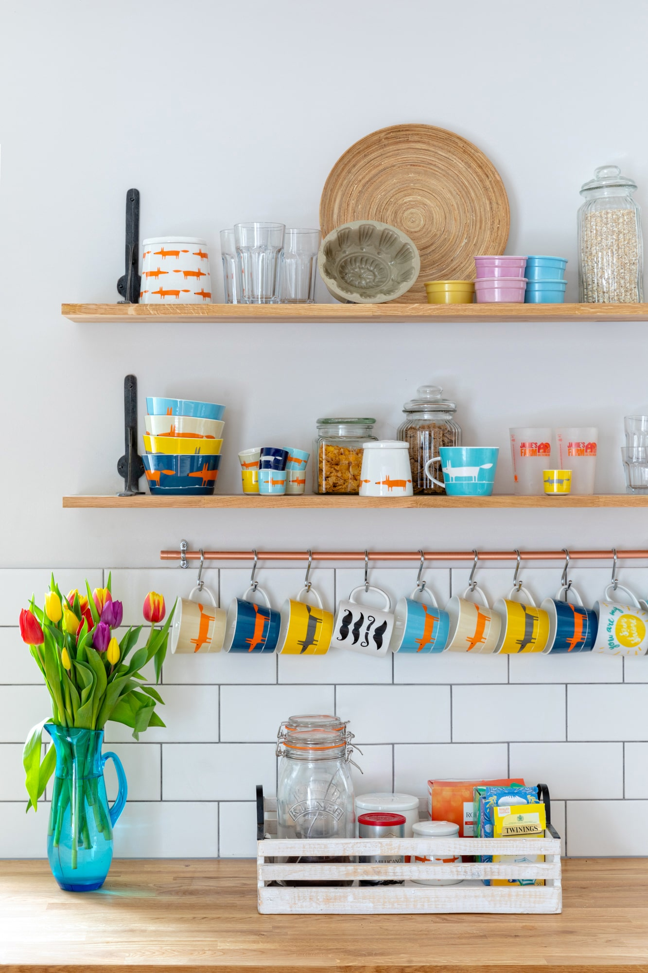 Interior detail shot: kitchen in the farm house,  shelves with mugs , jars, vase with tulips