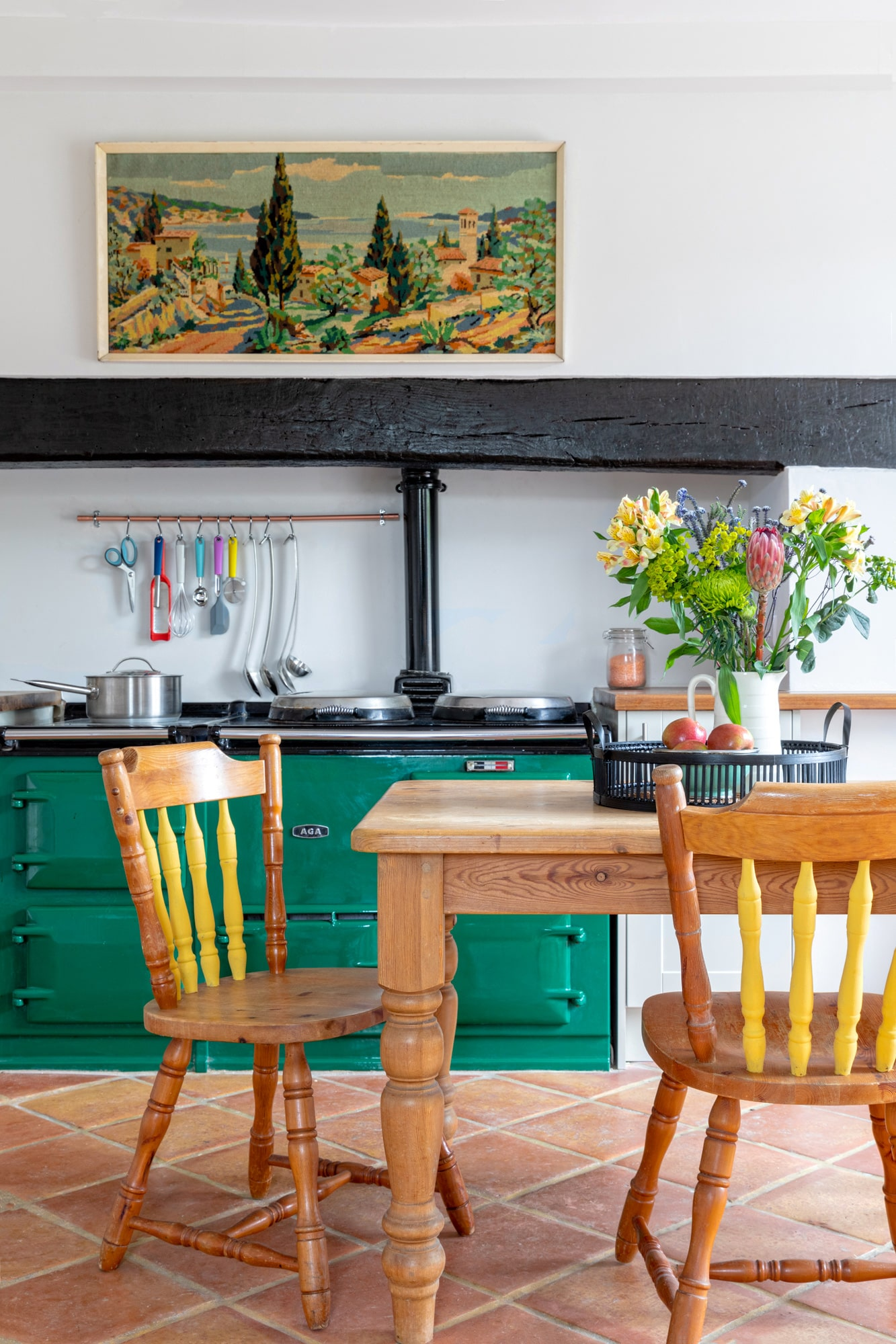 Interior photo of a kitchen in a farm house, a wooden table and chairs, aga hob