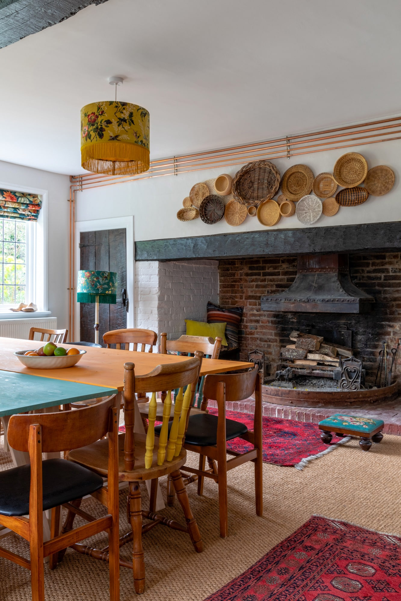 country house photo: colourful dining room, wooden tables, fireplace and woven baskets above it