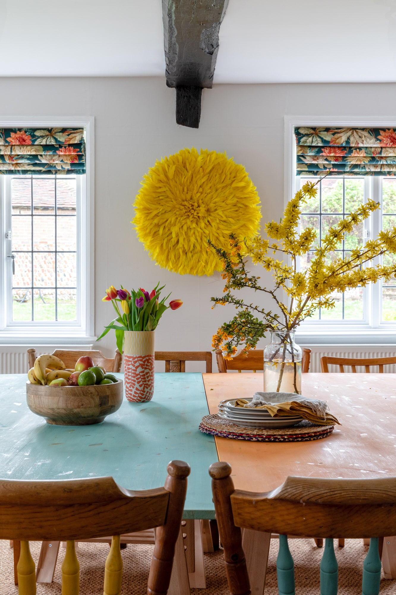 Interior detail photo of a dining room in a farm house: wooden table with v2 vases with vivid flowers, yellow accessory on the wall made of feathers