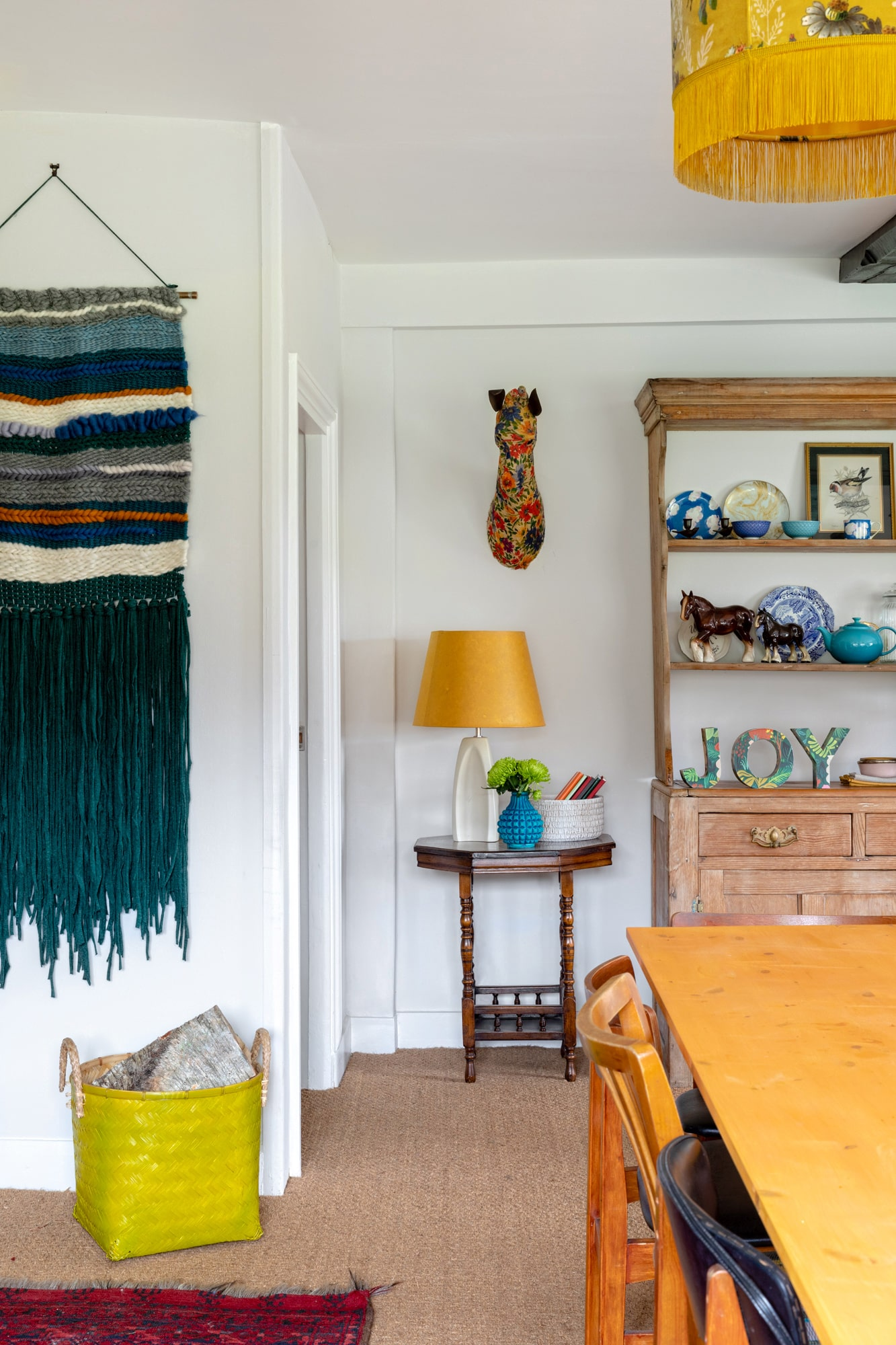 interior shot: colourful dining room in a farm house, wooden table, cabinet with tableware