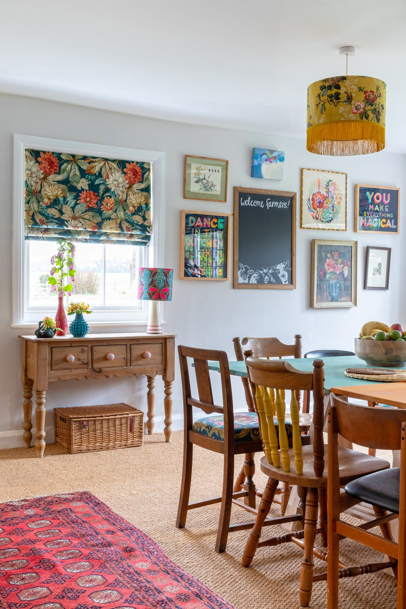 interior photo: colourful dining room, with art, wooden table, chairs, floral print on the roller curtains