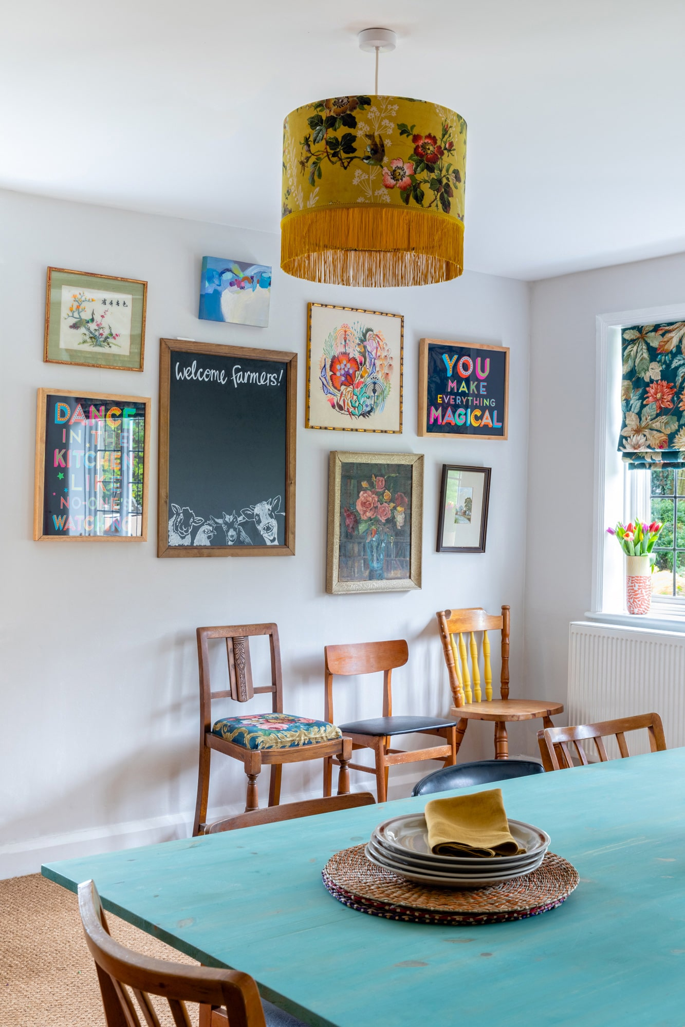 Dining room in a farm house: art on the wall, yellow ceiling lamp, chairs next to the wall and wooden table with plates