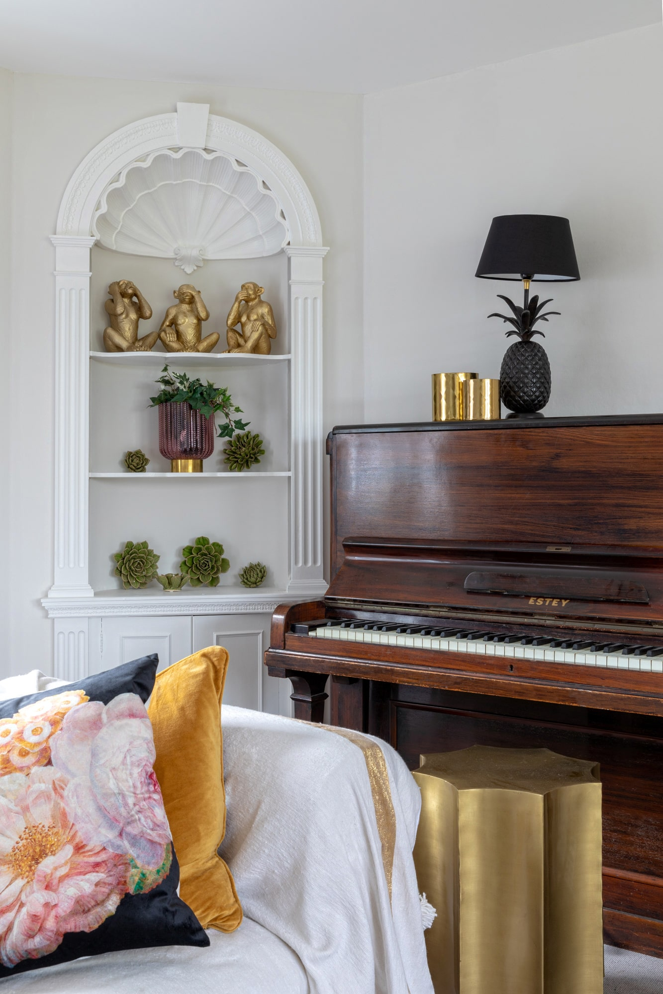 interior detail photo: sitting room in a farm house; piano; sofa covered with white throw with decorative cushions; shelves with accessories