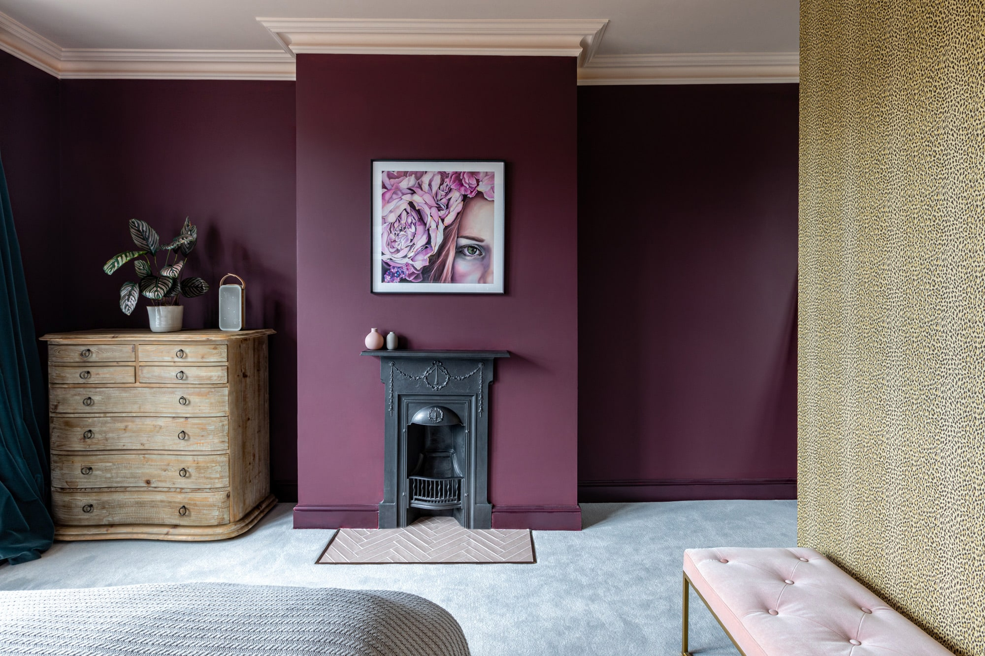 Interior design photography: bedroom with dark burgundy walls;  art with a girl in a flower band; fireplace; teal velvet curtains; bed; wooden chest of drawers; animal print feature wall
