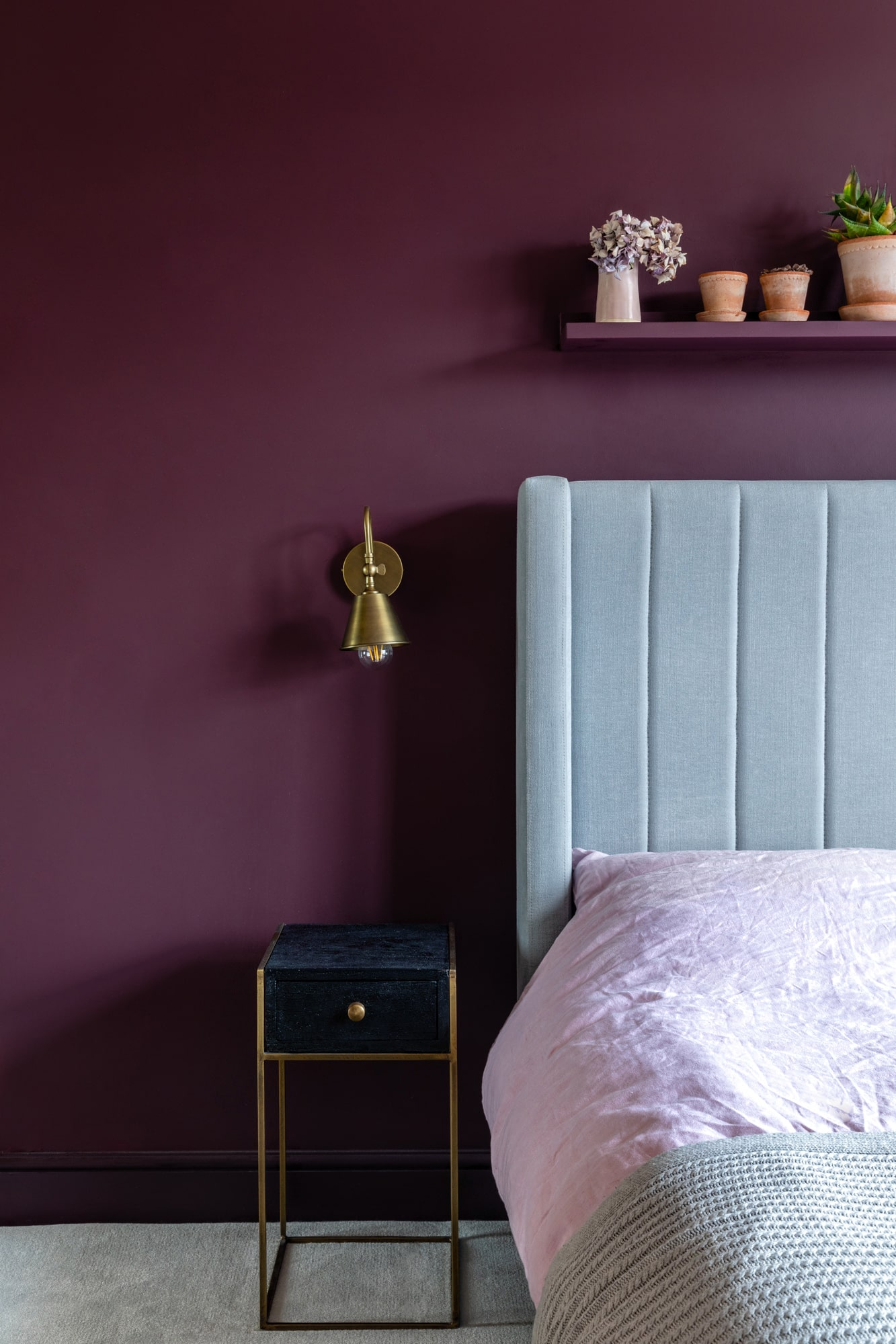 Interior detail shot: bedroom with dark burgundy walls; light blue bed, black bedside table, gold lamp, a shelf with succulents