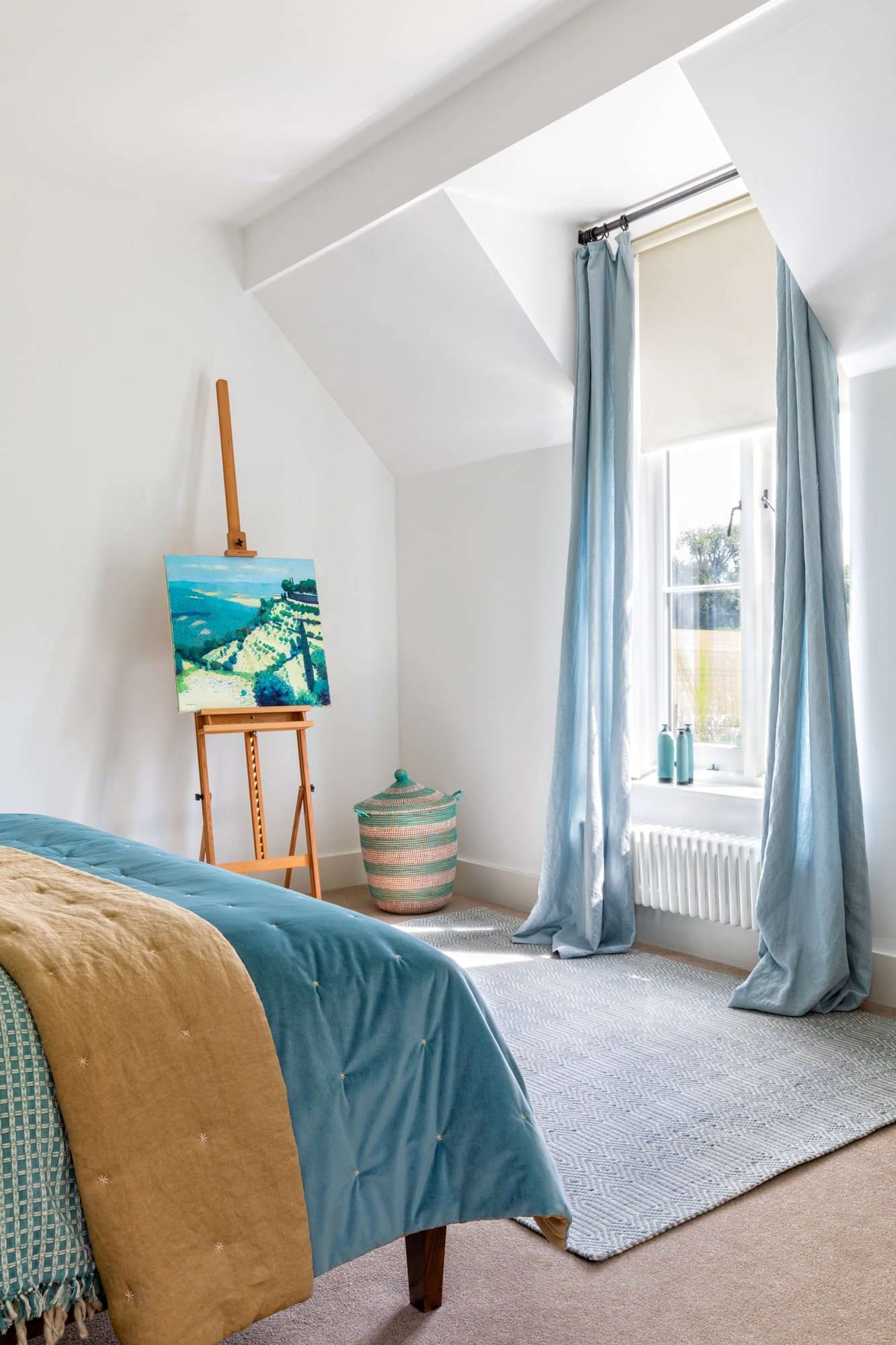 Interior photo: bedroom in a country house, a corner of bed with blue cover, blue curtains and art on easel