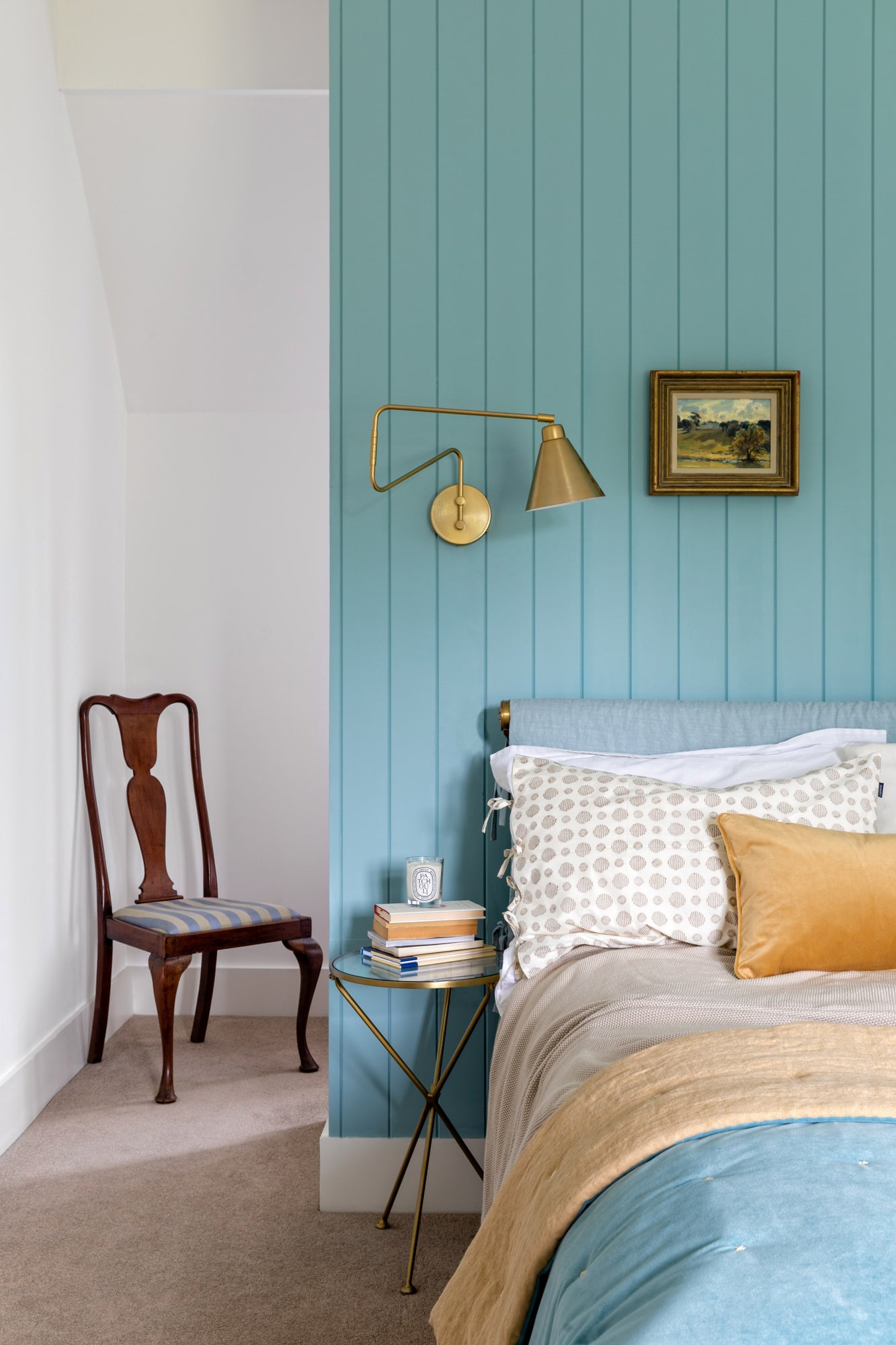 Interior photo: bedroom in a country house with blue wooden paneling, wide bed, gold hanging light on the left side and a chair