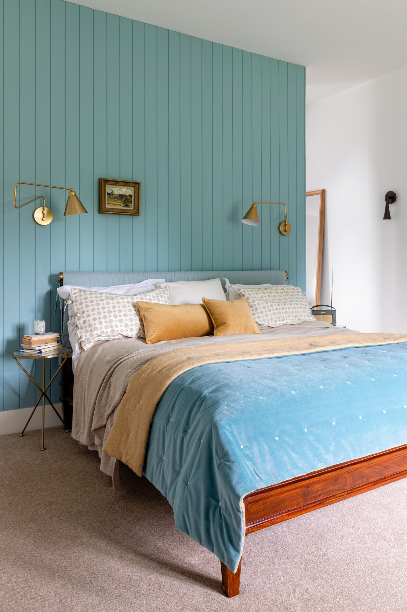 Interior photo: bedroom in a country house with blue wooden paneling, wide bed, gold hanging lights on each side