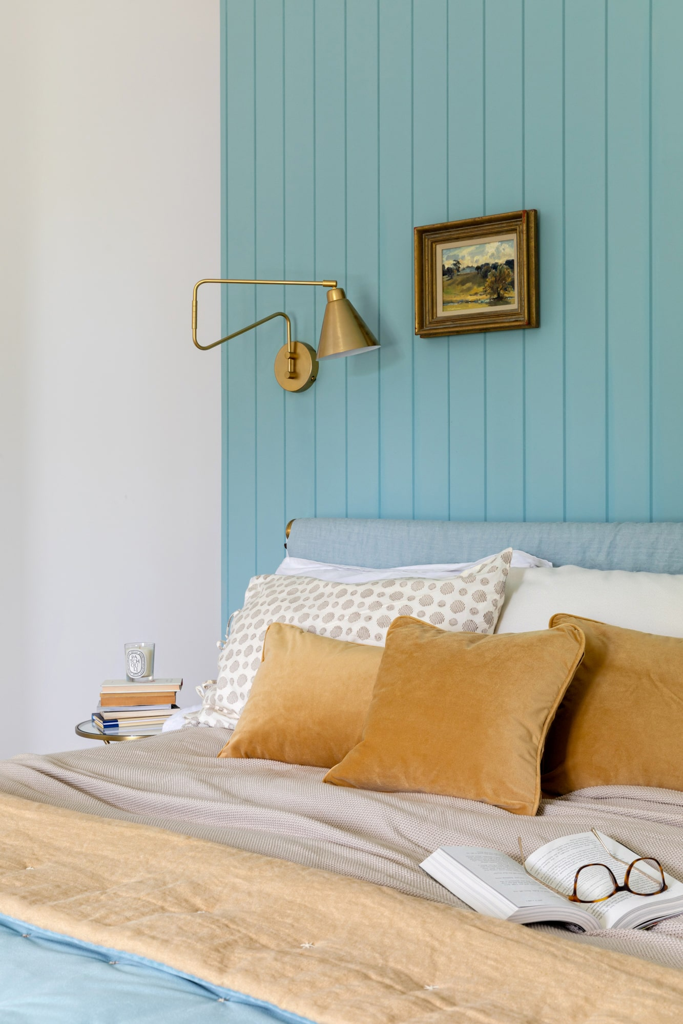 Interior photo: bedroom in a country house with blue wooden paneling, detail of a bed bed, gold hanging light, small painting and yellow pillows