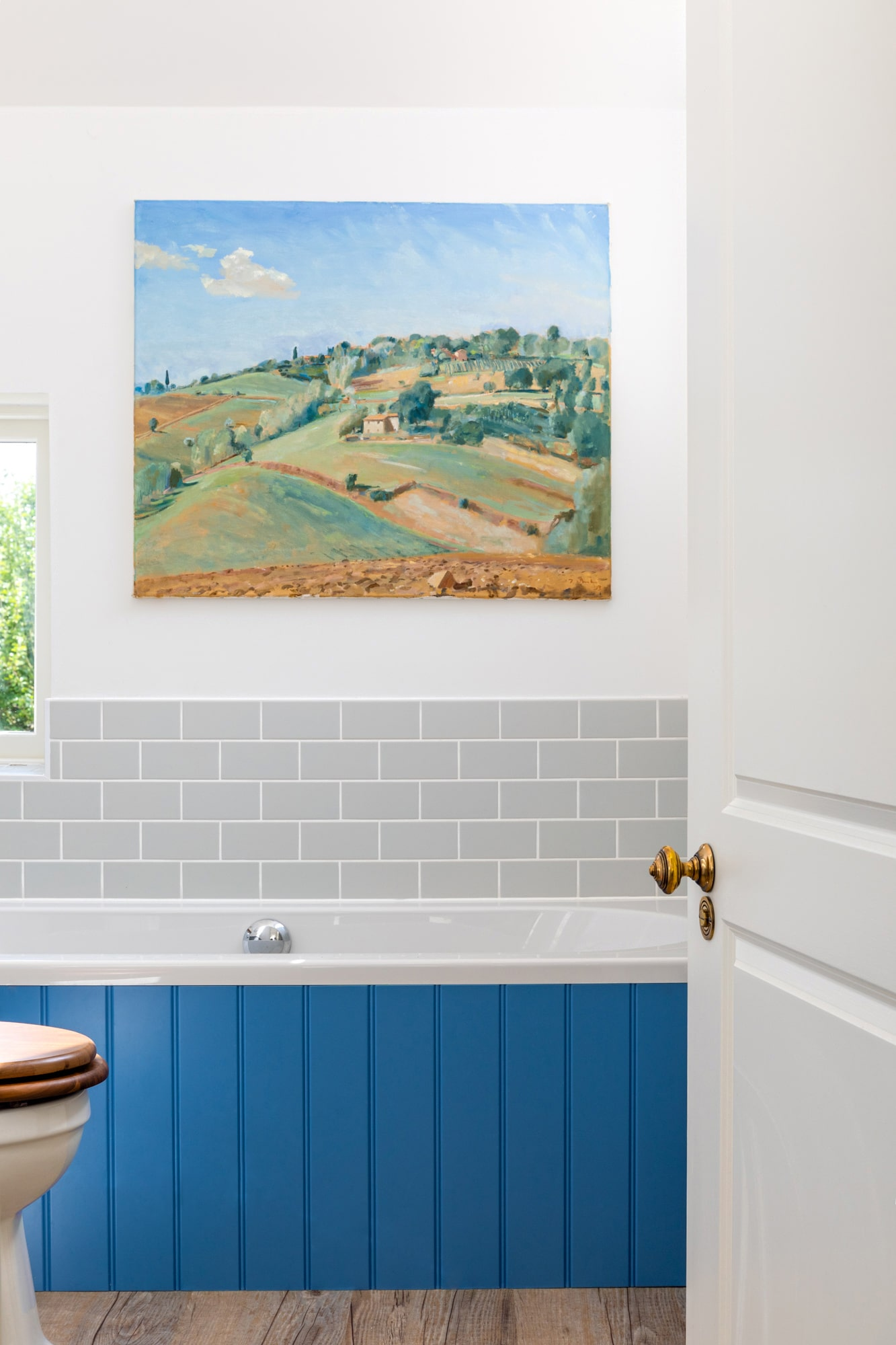 Interior design photography: bathroom in a country house with blue paneling on a bathtub, landscape art on the wall