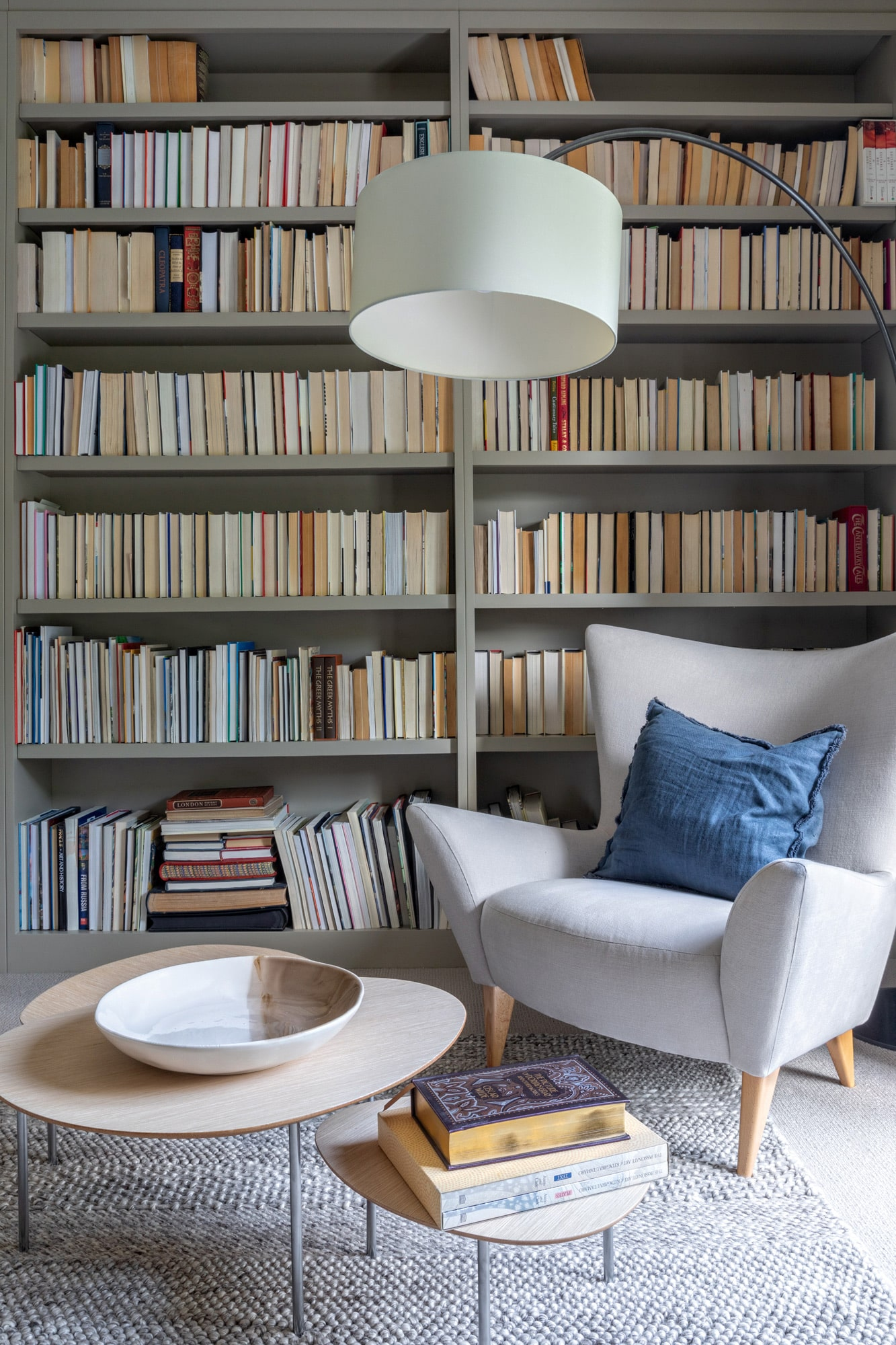Interior photo: library in a country house; shelves with books, a high standing lamp, a grey armchair and a coffee table