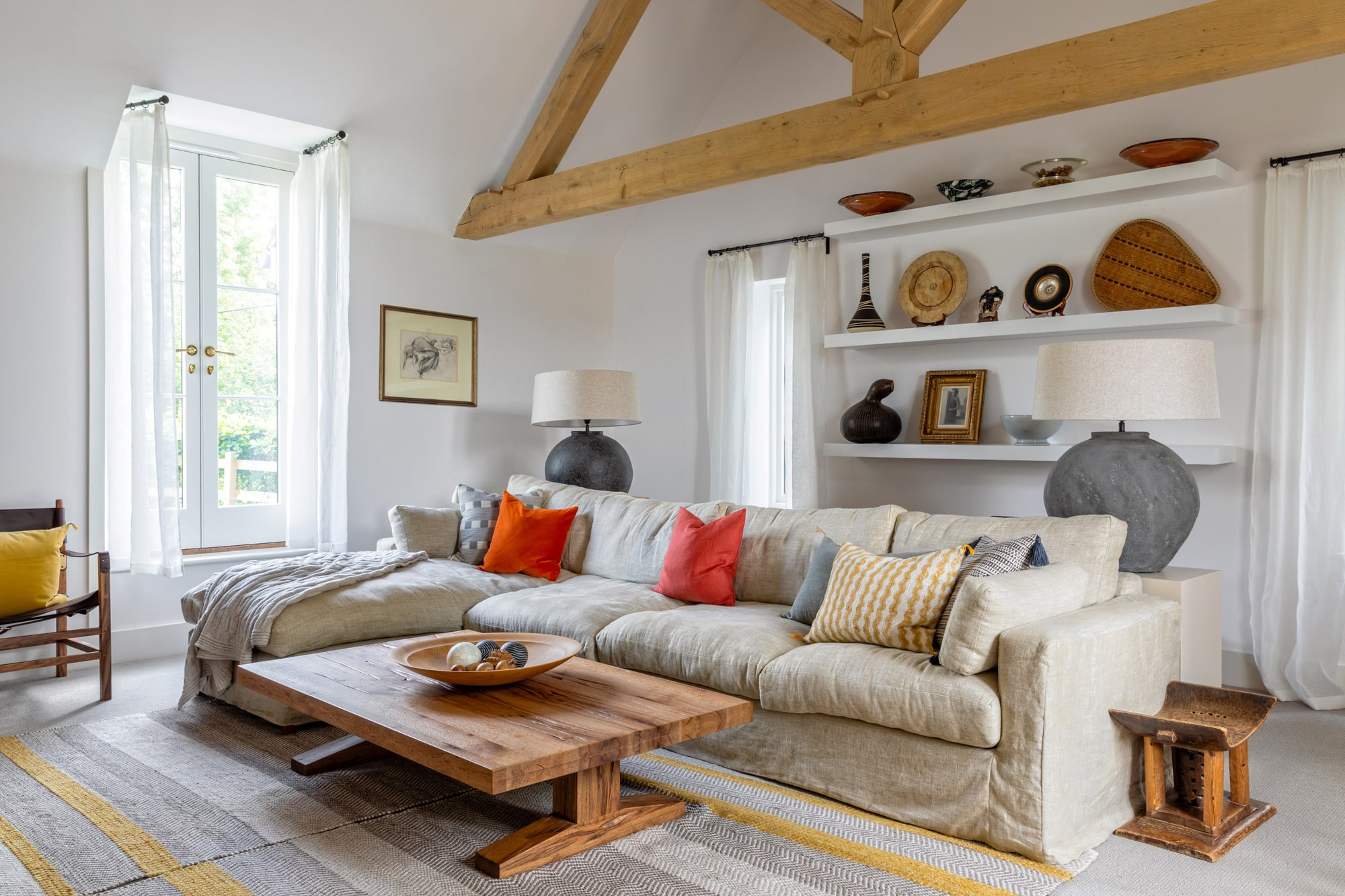 Interior photography of a country house: living room detail, a grey sofa with pillows; white shelves with cute accessories; a wooden coffee table