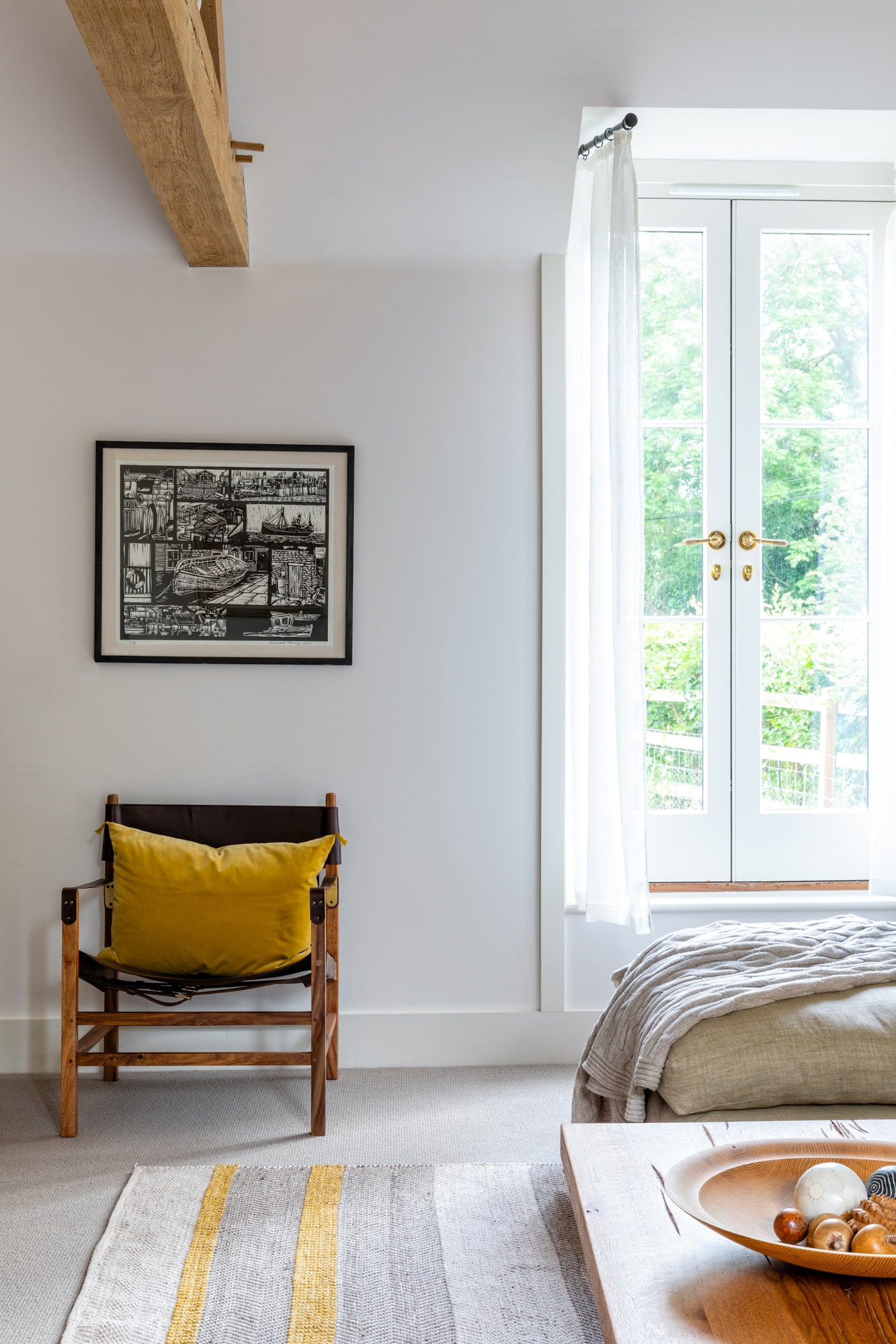 detail Interior design photo of a living room: a a chair with a yellow pillow next to a window with an above it, grey sofa