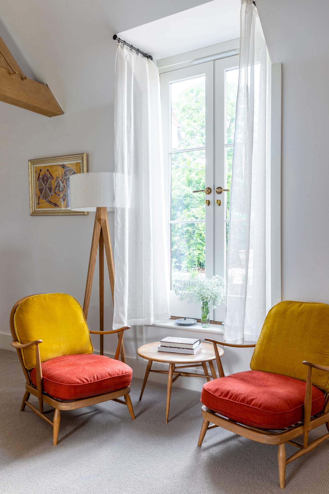 Interior design photo: two yellow and red armchairs in front of the window in a farm house
