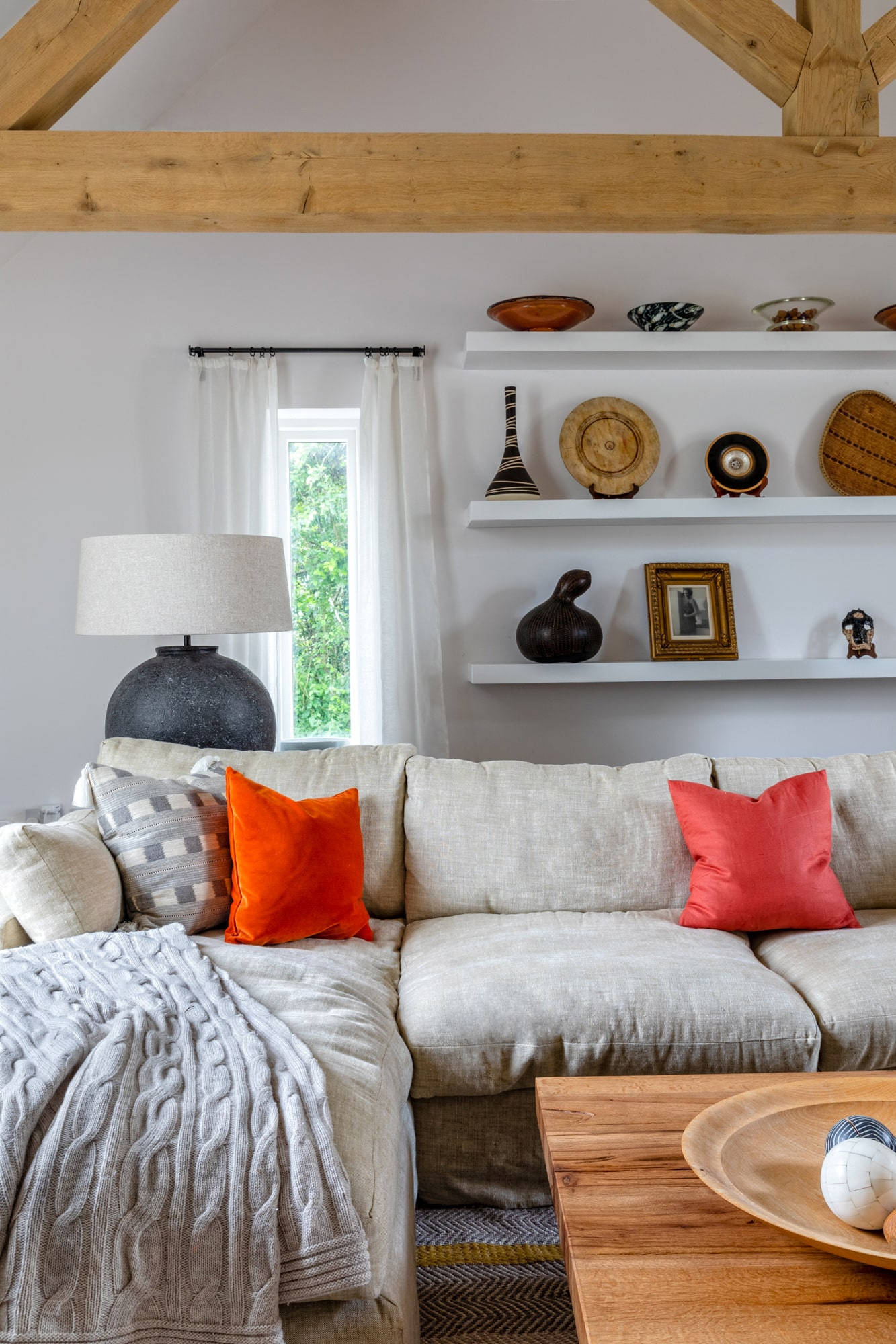 Interior photography: living room detail, a grey sofa with pillows; white shelves with cute accessories