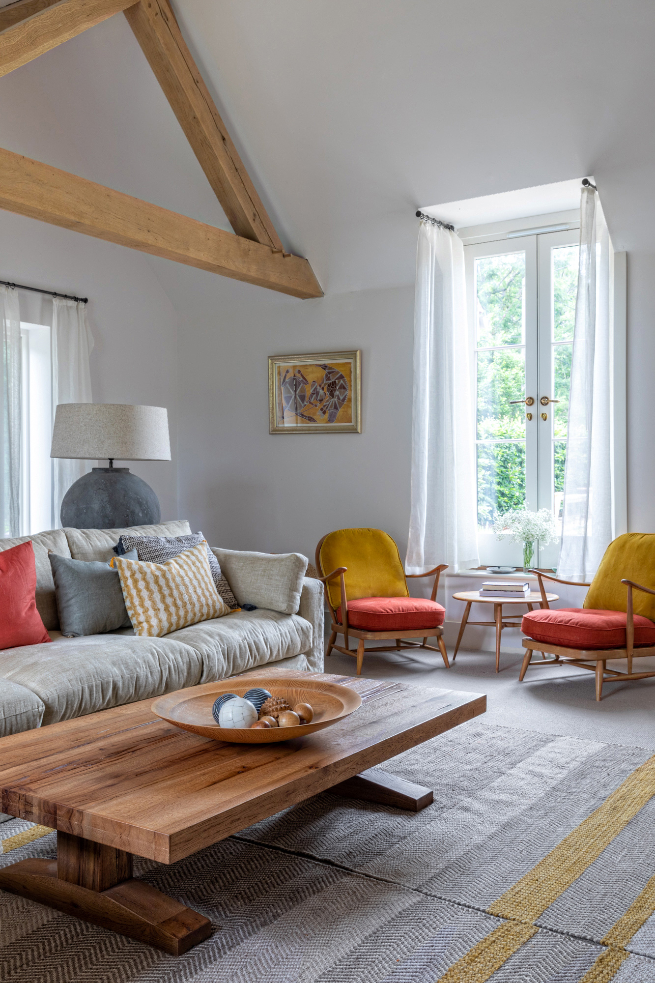 Interior design photo: two yellow and red armchairs in front of the window in a farm house; grey sofa and wooden coffee table