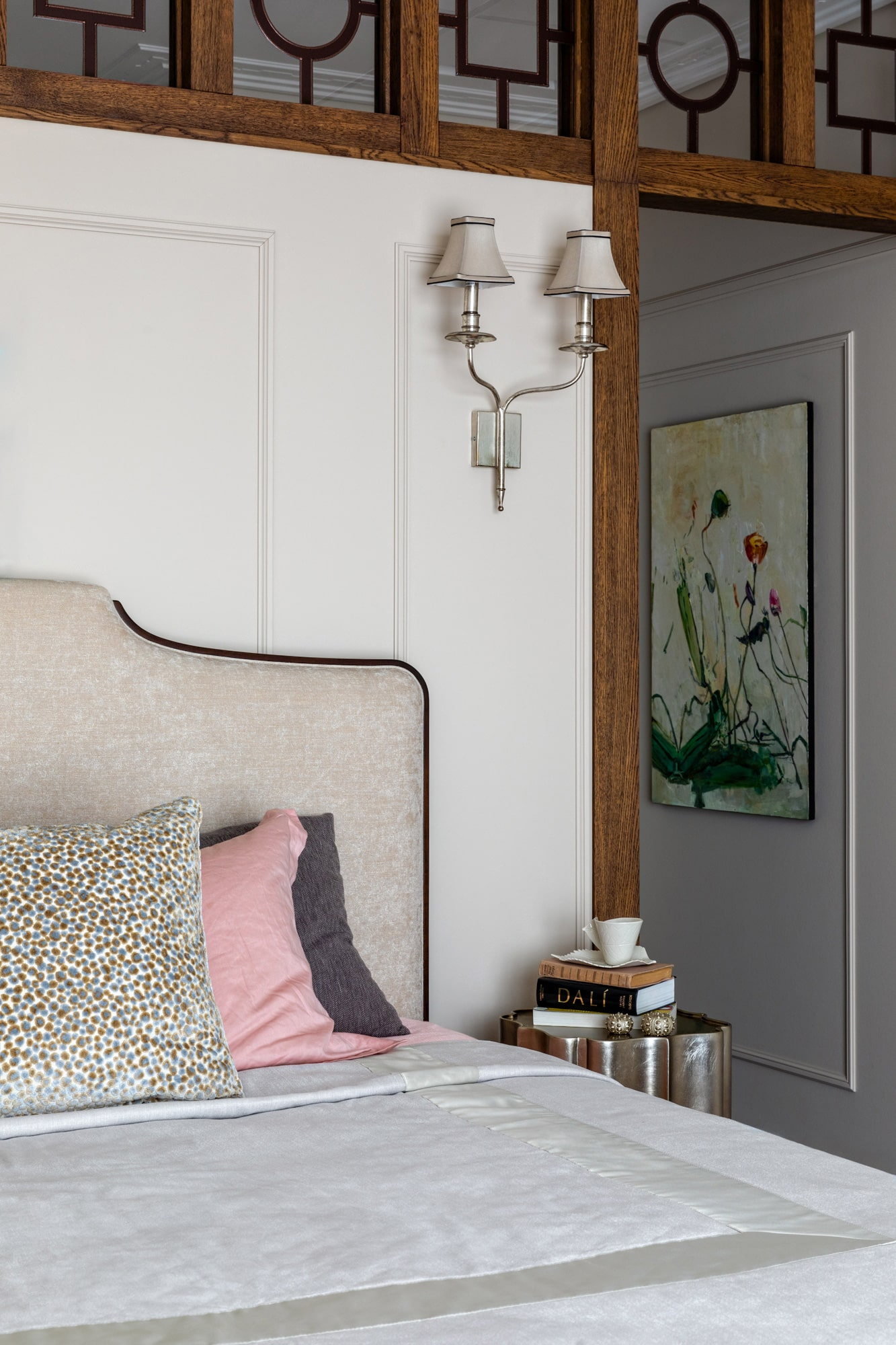 interior detail shot: bedroom with beige warm walls, beige bed; bedside table with books and a painting on the wall