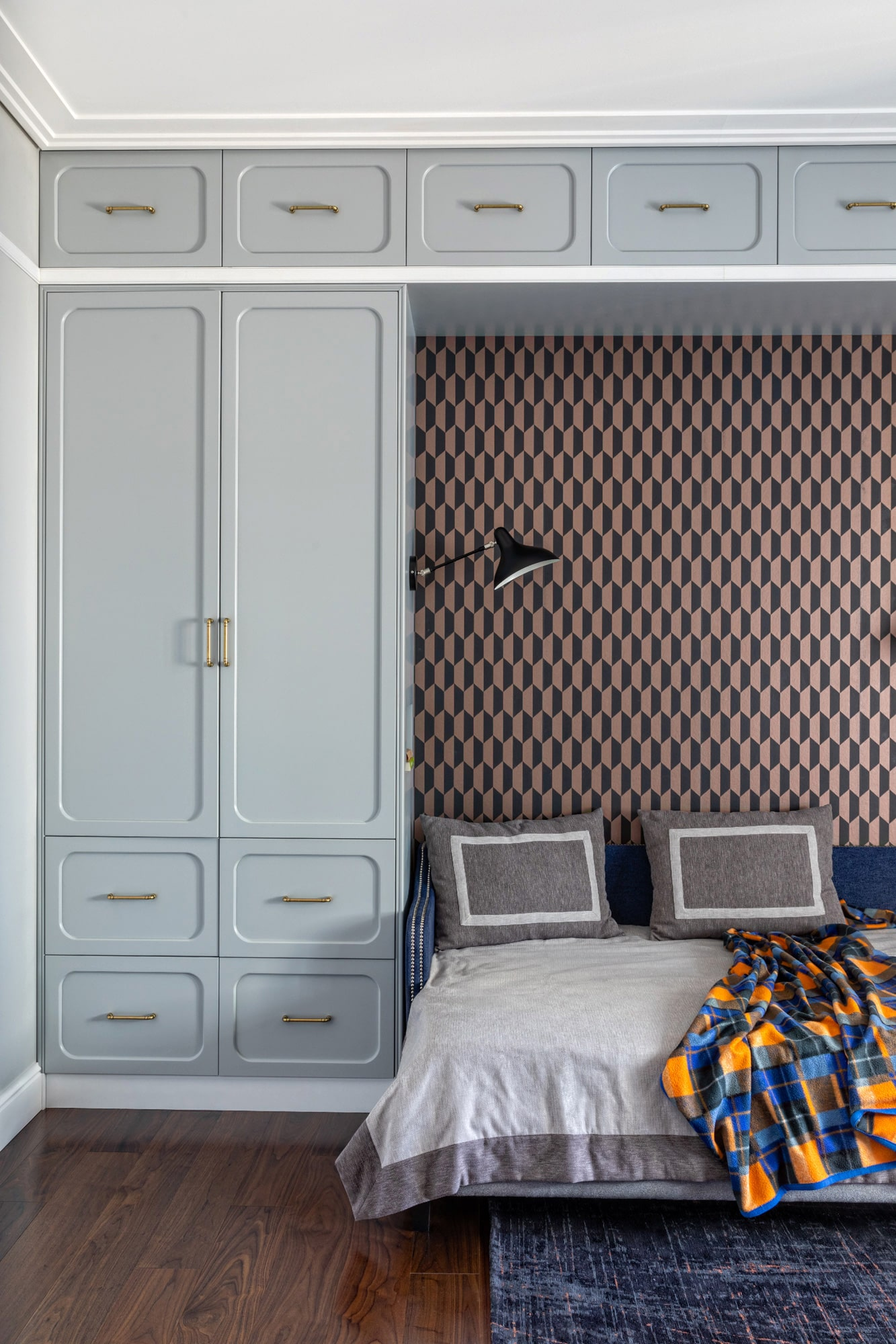 detail interior shot: teenager's bedroom, patterned wallpaper, grey wardrobe, a small sofa bed
