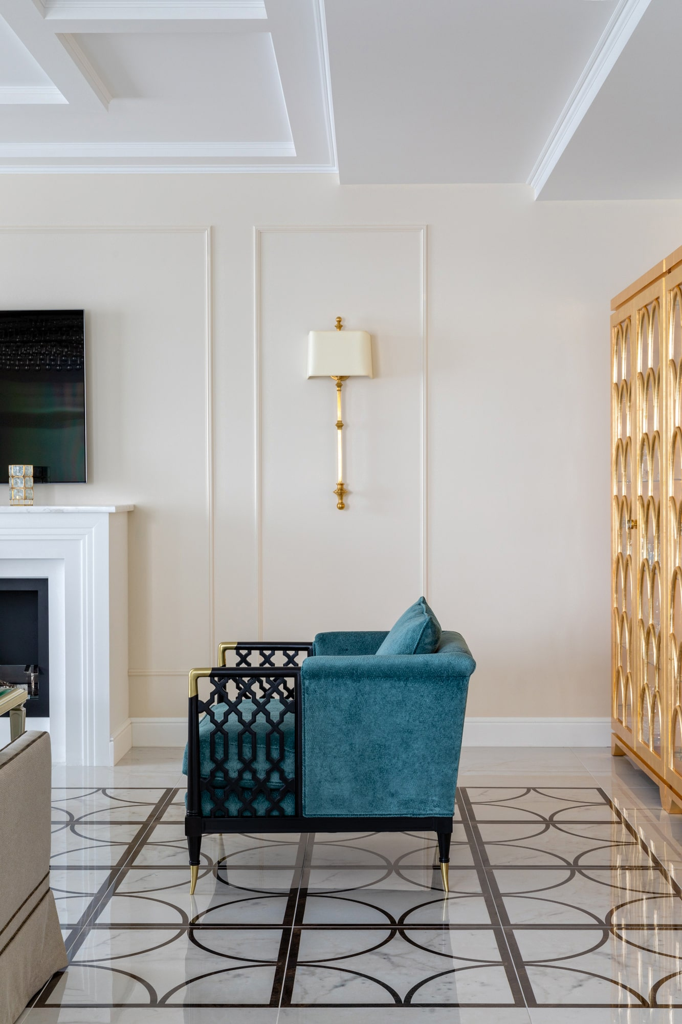 Living room interior detail photo: teal velvet armchair; marble looking tiles, gold cabinet
