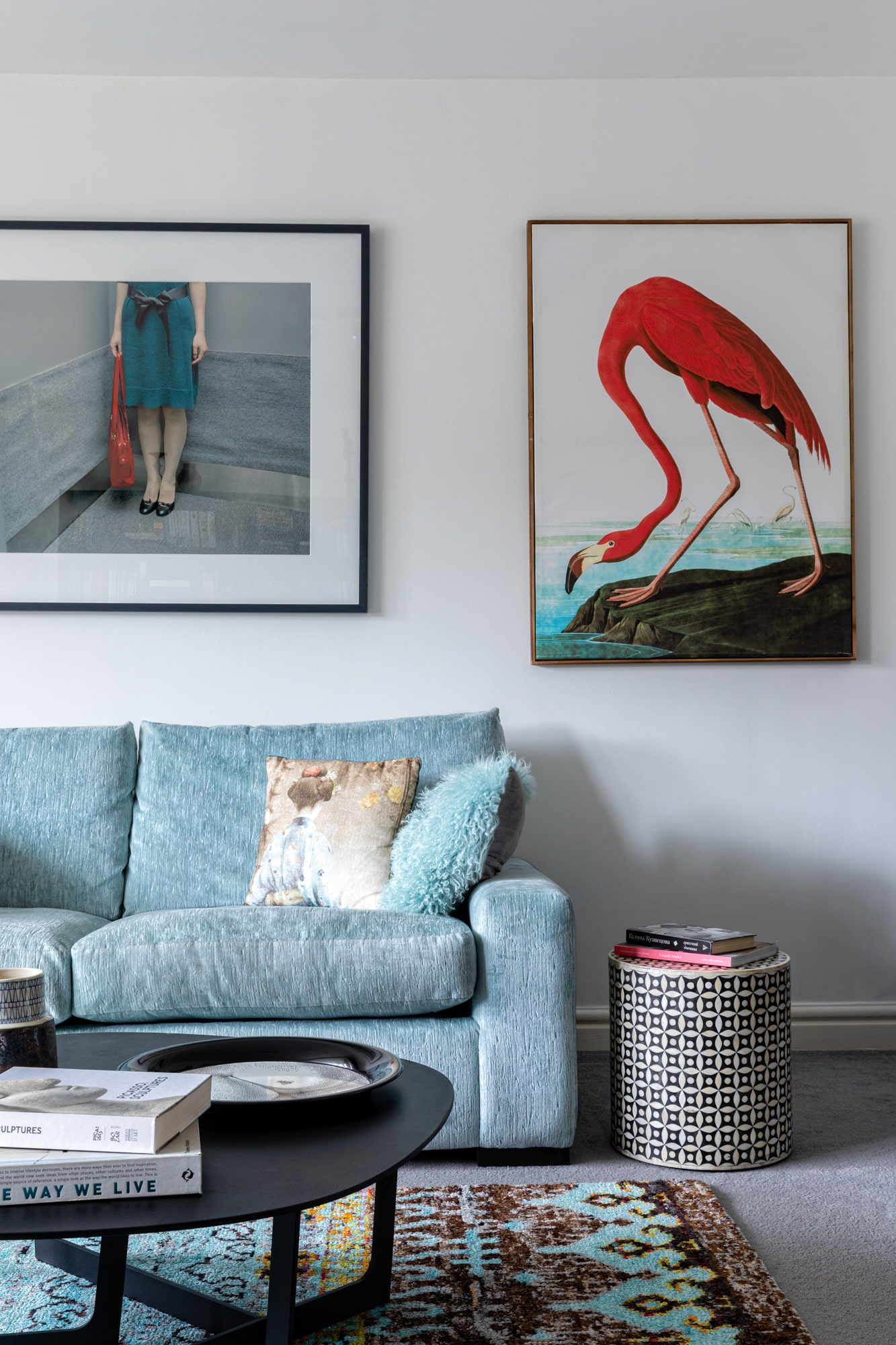 Interior design photography: a detail shot of a living room with light blue velvet sofa, fluffy pillow, a poster of Japanese girl in a lift; on the left side of the poster is an art with a red flamingo