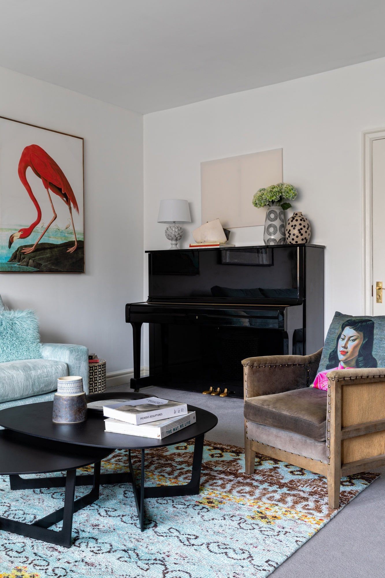 Interior photo: a living room design; a blue velvet sofa, coffee table, brown velvet armchair, black piano and a flamingo poster on the wall