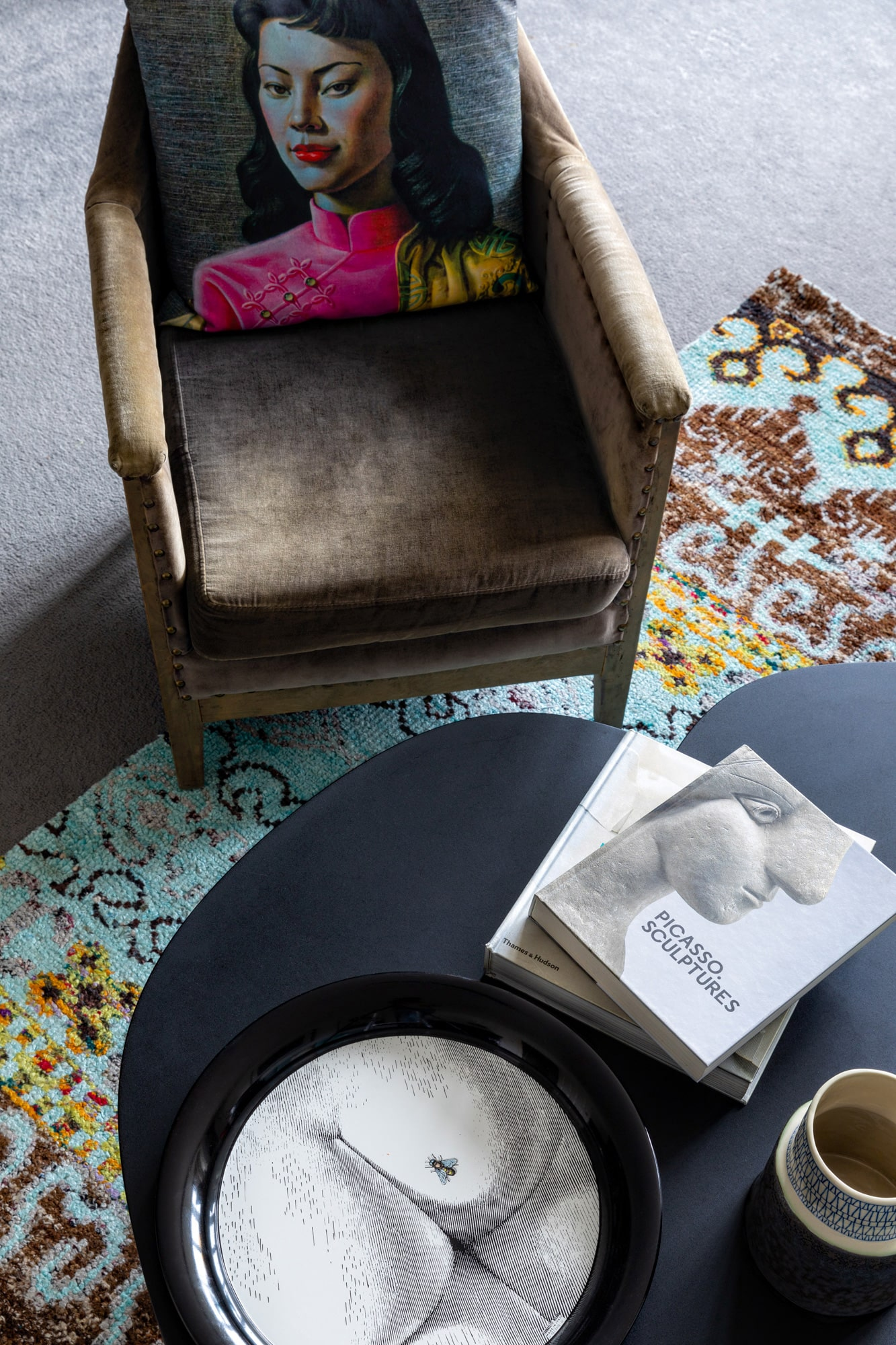 a detail interior photography image: a view from top down on a coffee table with books and tray on it and on a velvet armchair