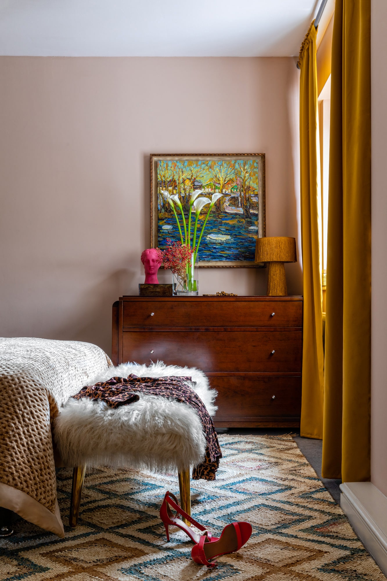 Interior photo: bedroom with salmon walls, yellow curtains, chest of drawers, colourful art, women's pink shoes on the floor by the bed