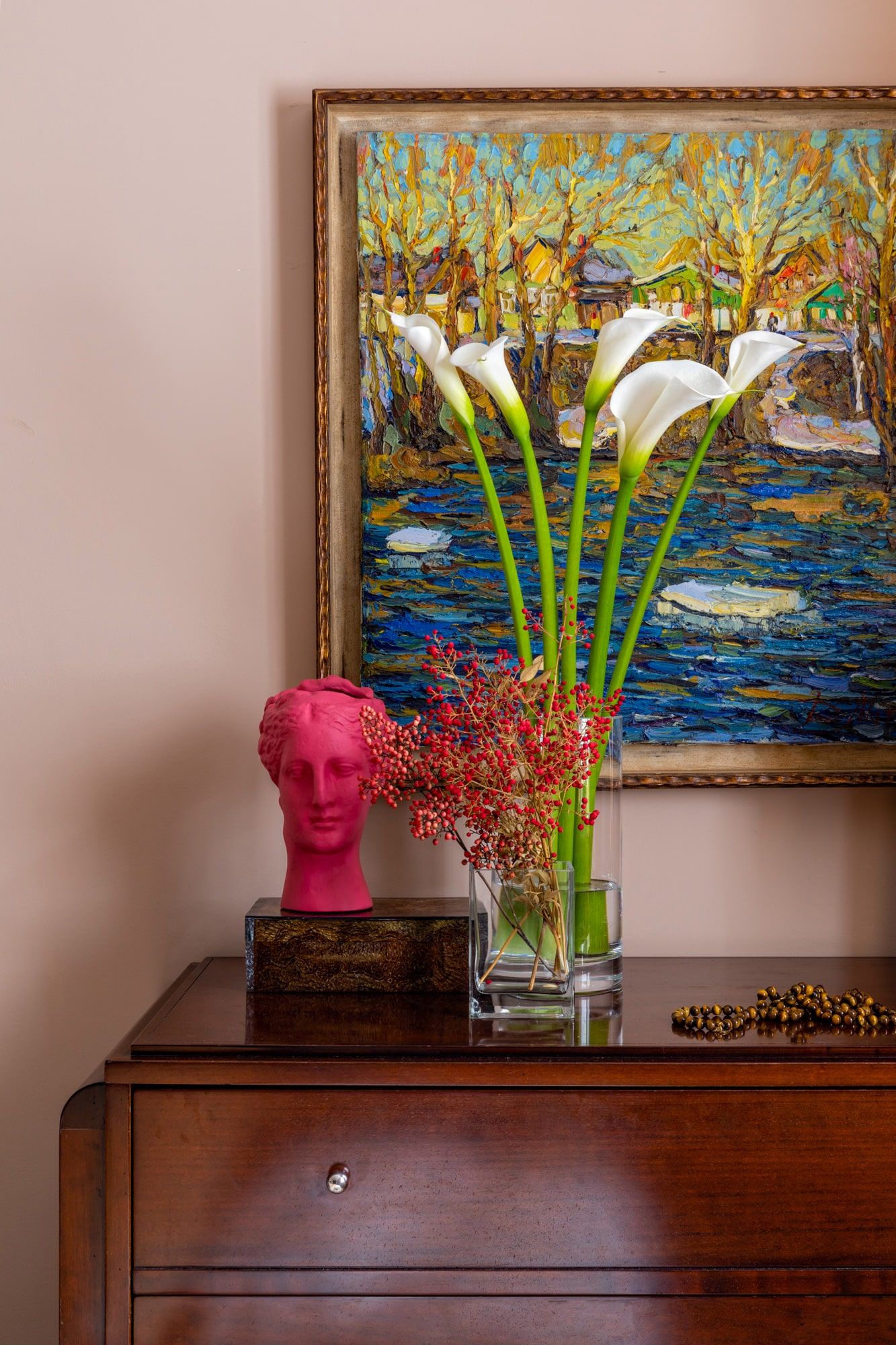 Detail interior photo of a bedroom: pink salmon wall, chest of drawers, with a red female bust  and a vase with white flowers on top; a vivid colors painting on the wall