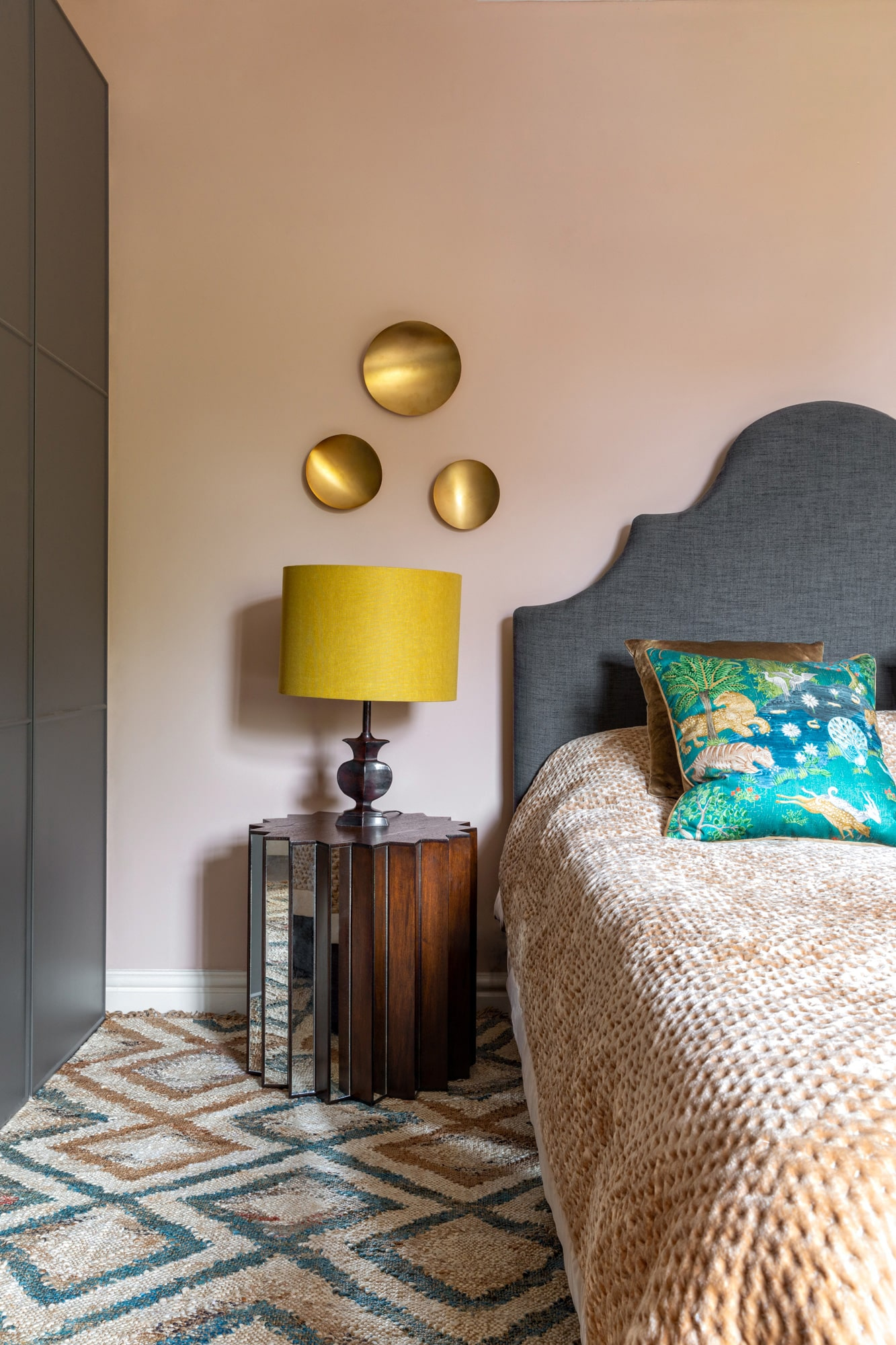 Interior photo: a bedroom with salmon pink walls, grey bed, grey wardrobe, glass bedside table with a yellow lamp on top