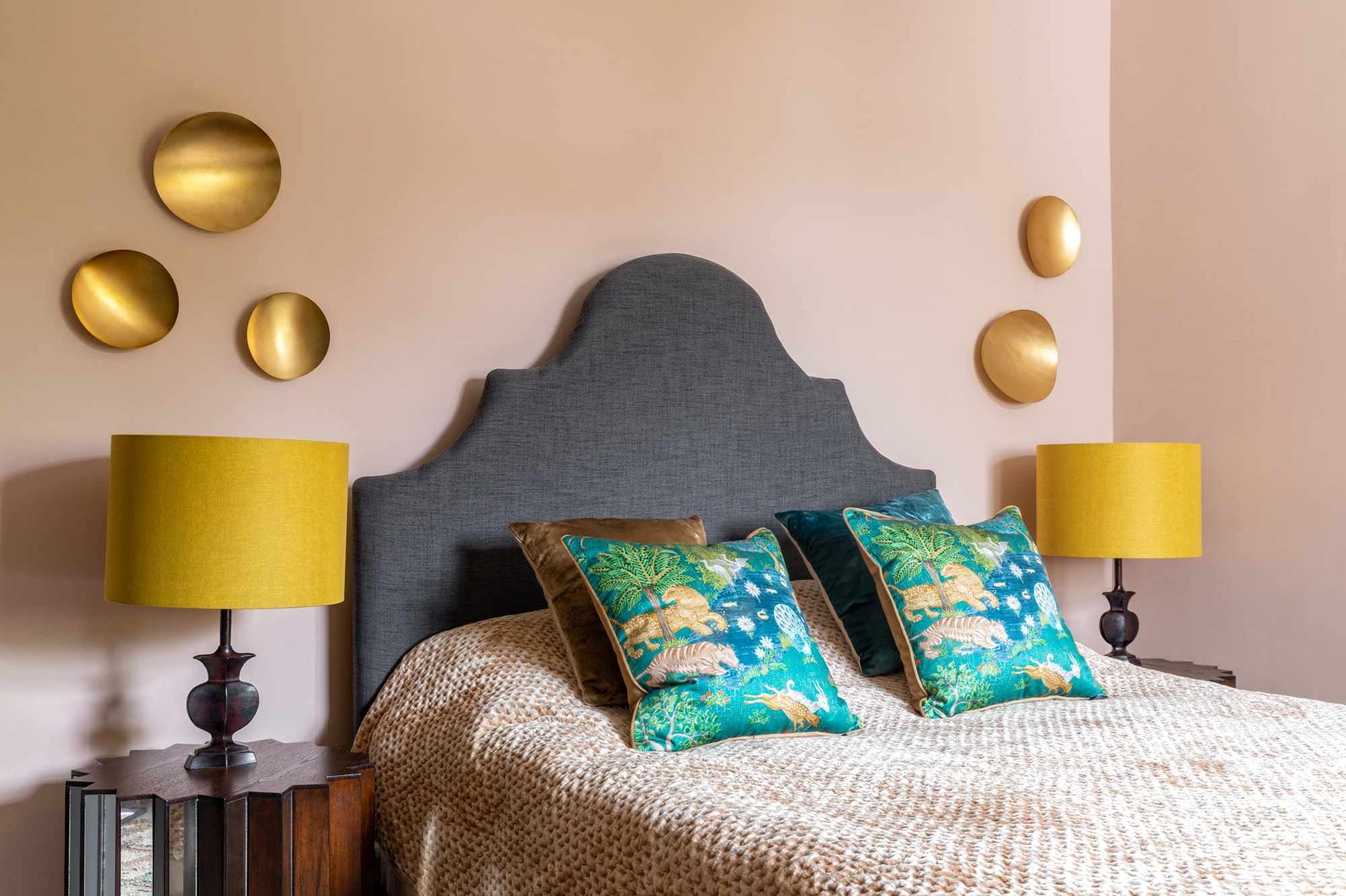 Interior photo: a bedroom with salmon pink walls, grey bed, glass bedside table with a yellow lamp on top