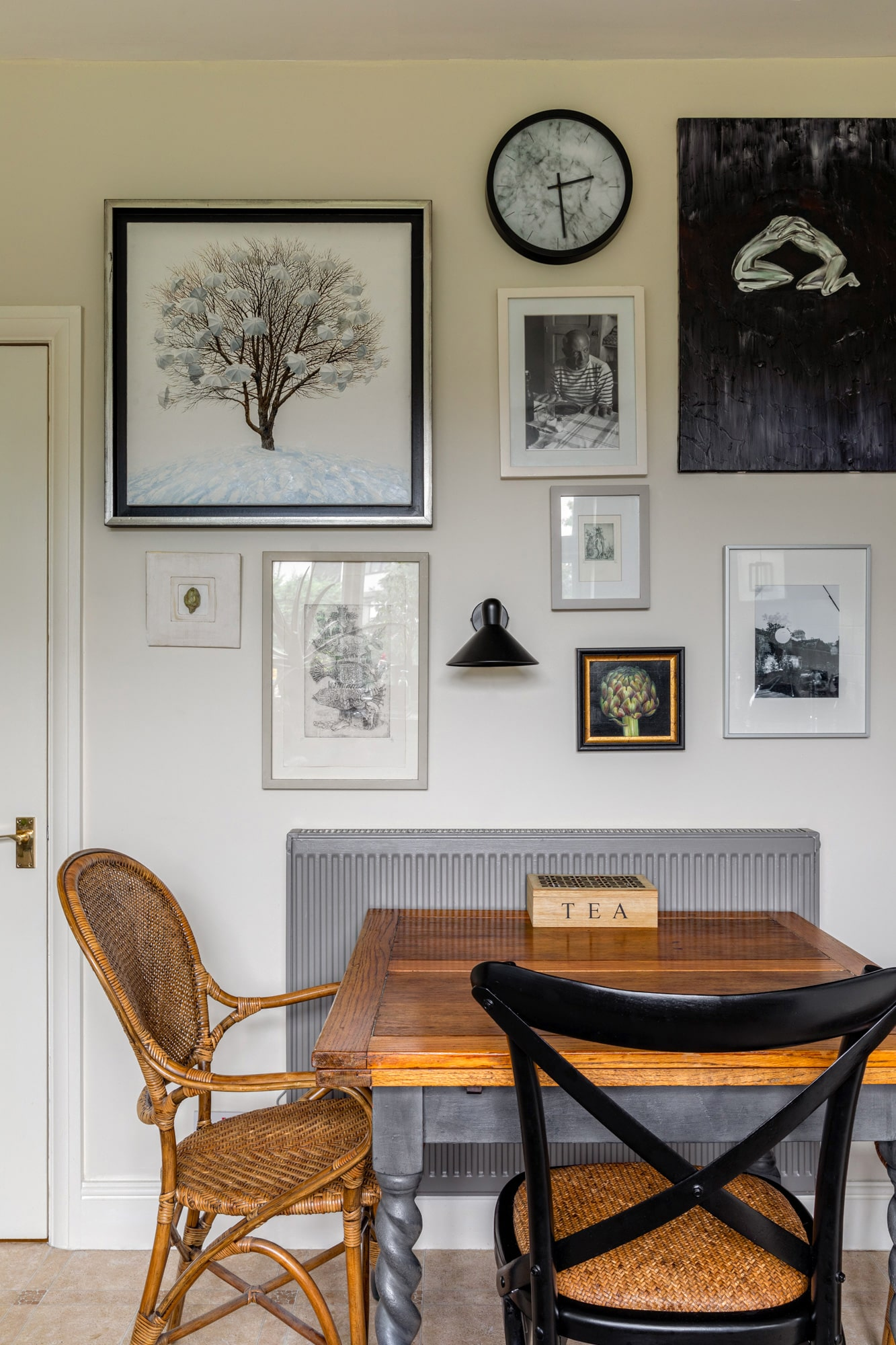 Interior design photo: kitchen with warm beige walls; wooden table with mismatched chairs and wall art
