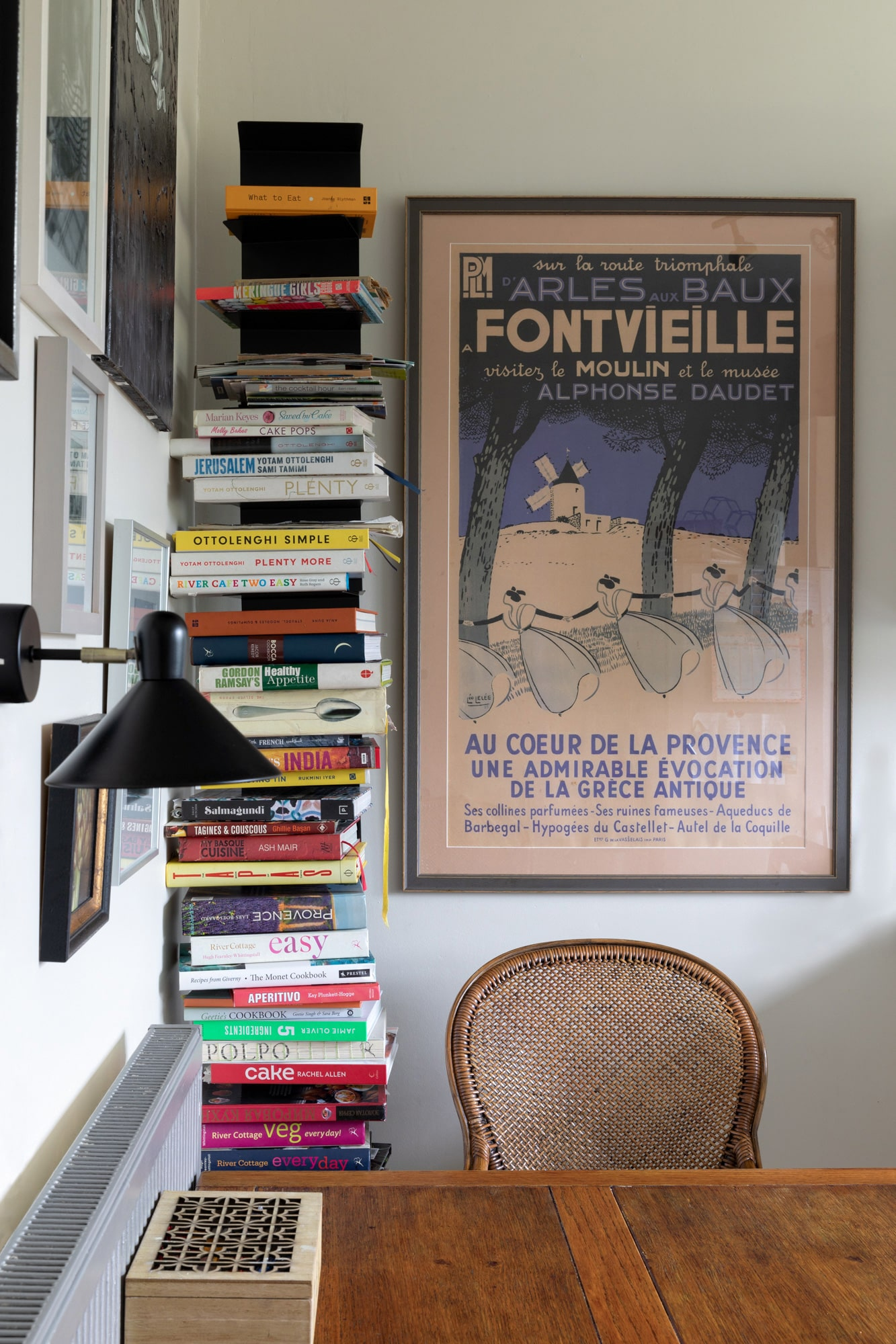 interior photo of a kitchen: pile of books near wooden table with a poster on the wall
