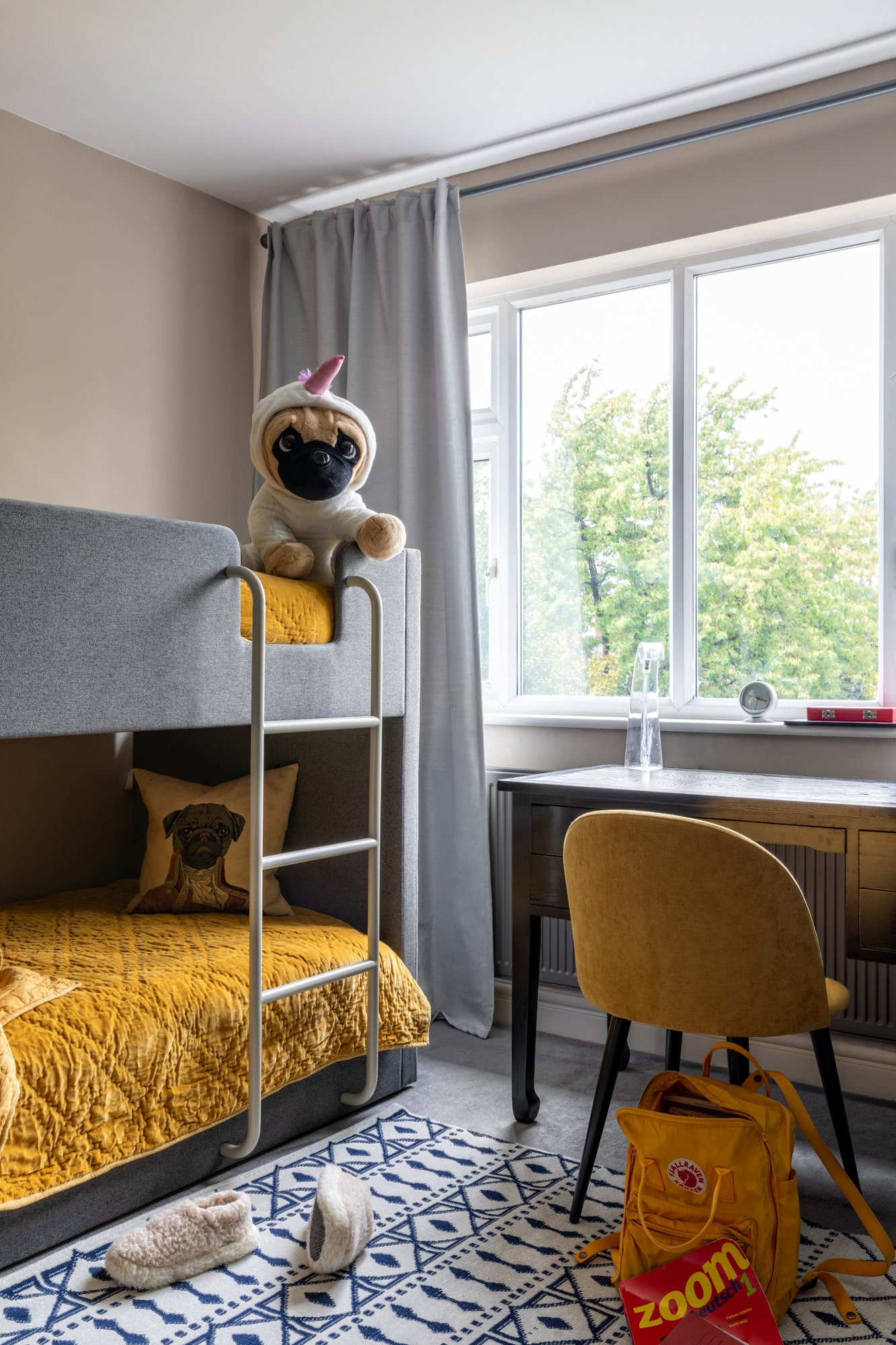 interior photo: kids room; bunk bed with yellow cover, a toy dog on the second level of the bulk bed; a desk and yellow chair
