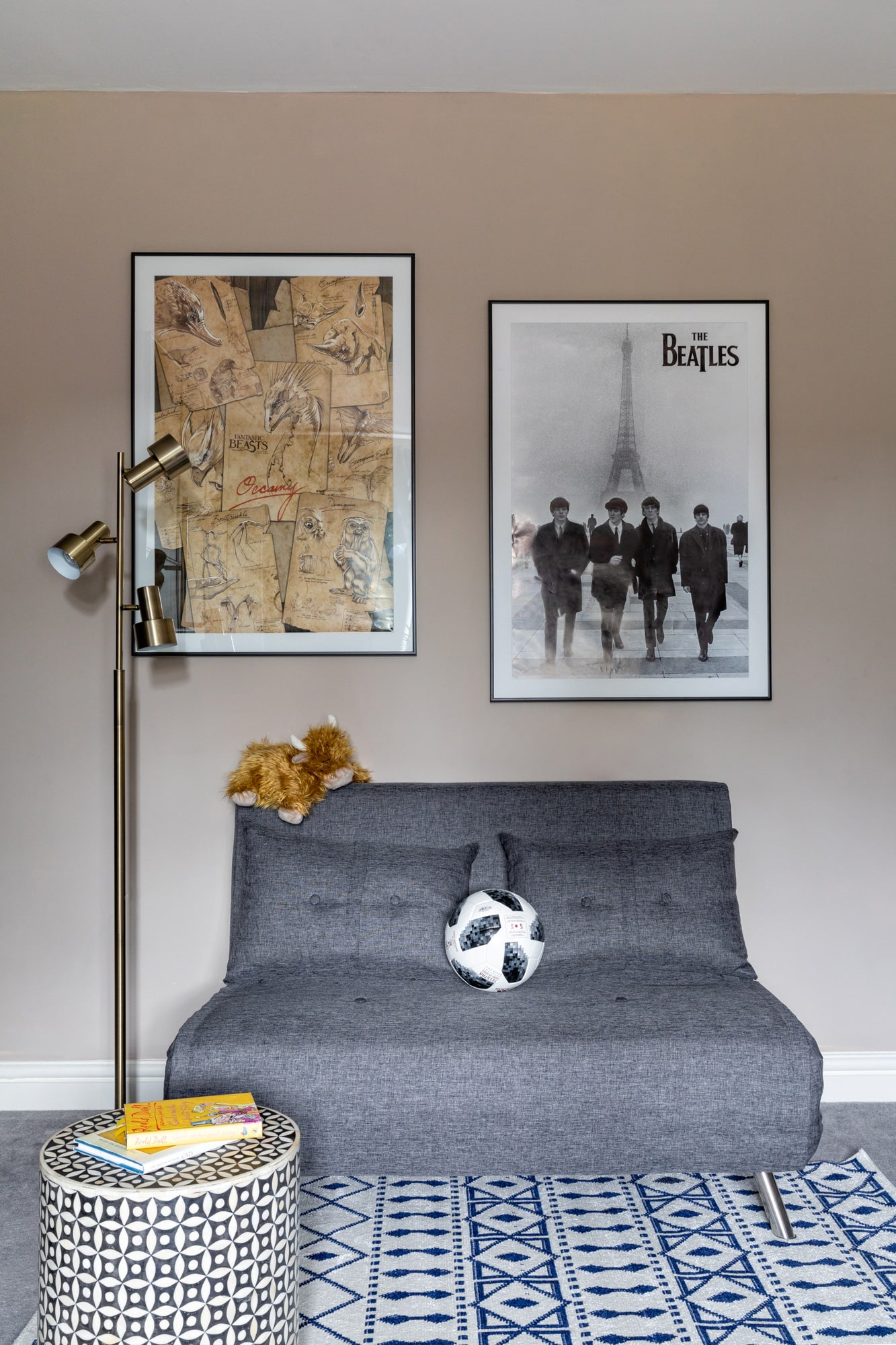 detail interior photo of a kids room: a small grey sofa; Beatles poster and a map on the wall