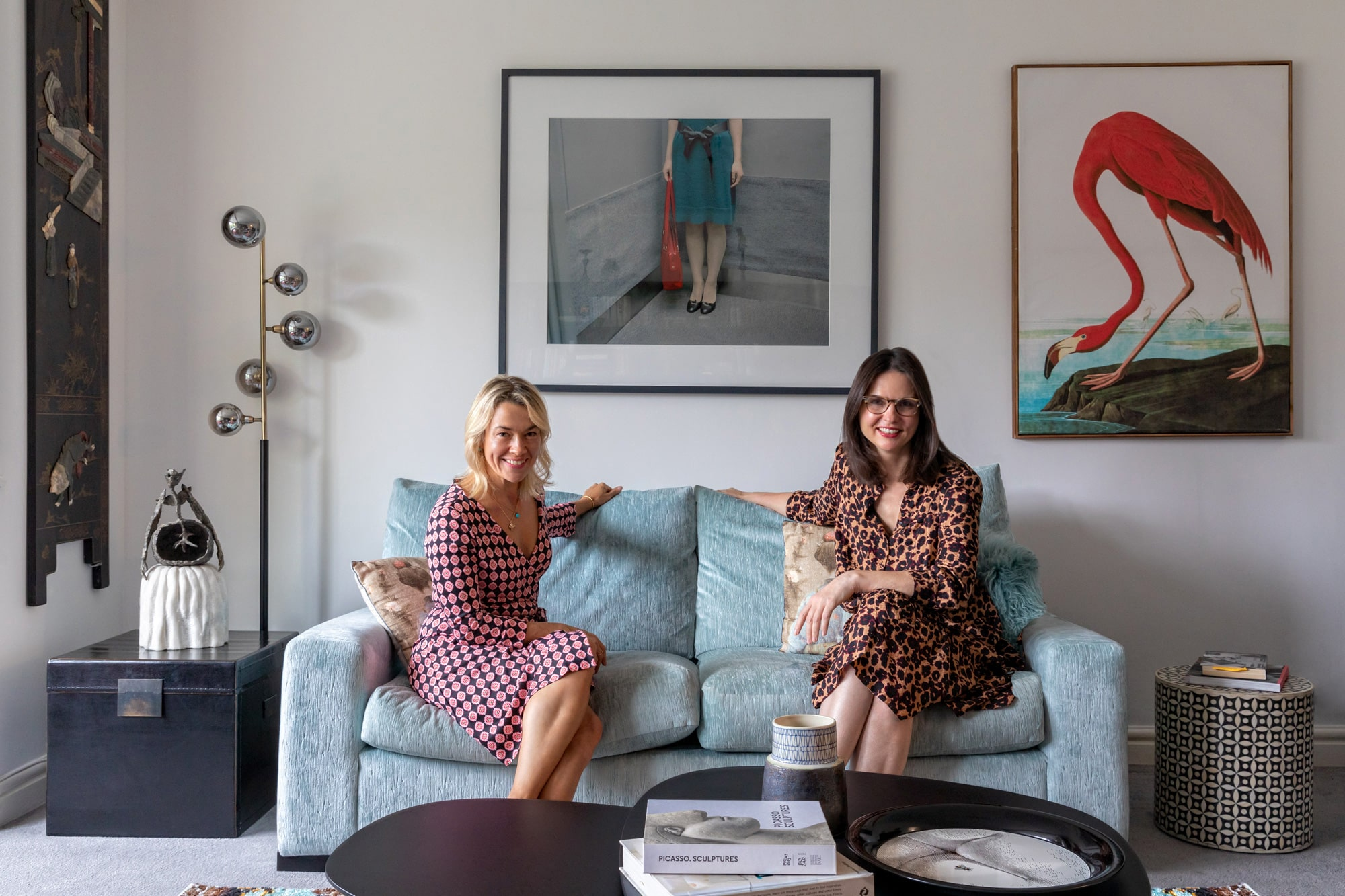 a portrait of two female interior designers sitting on a light blue velvet sofa