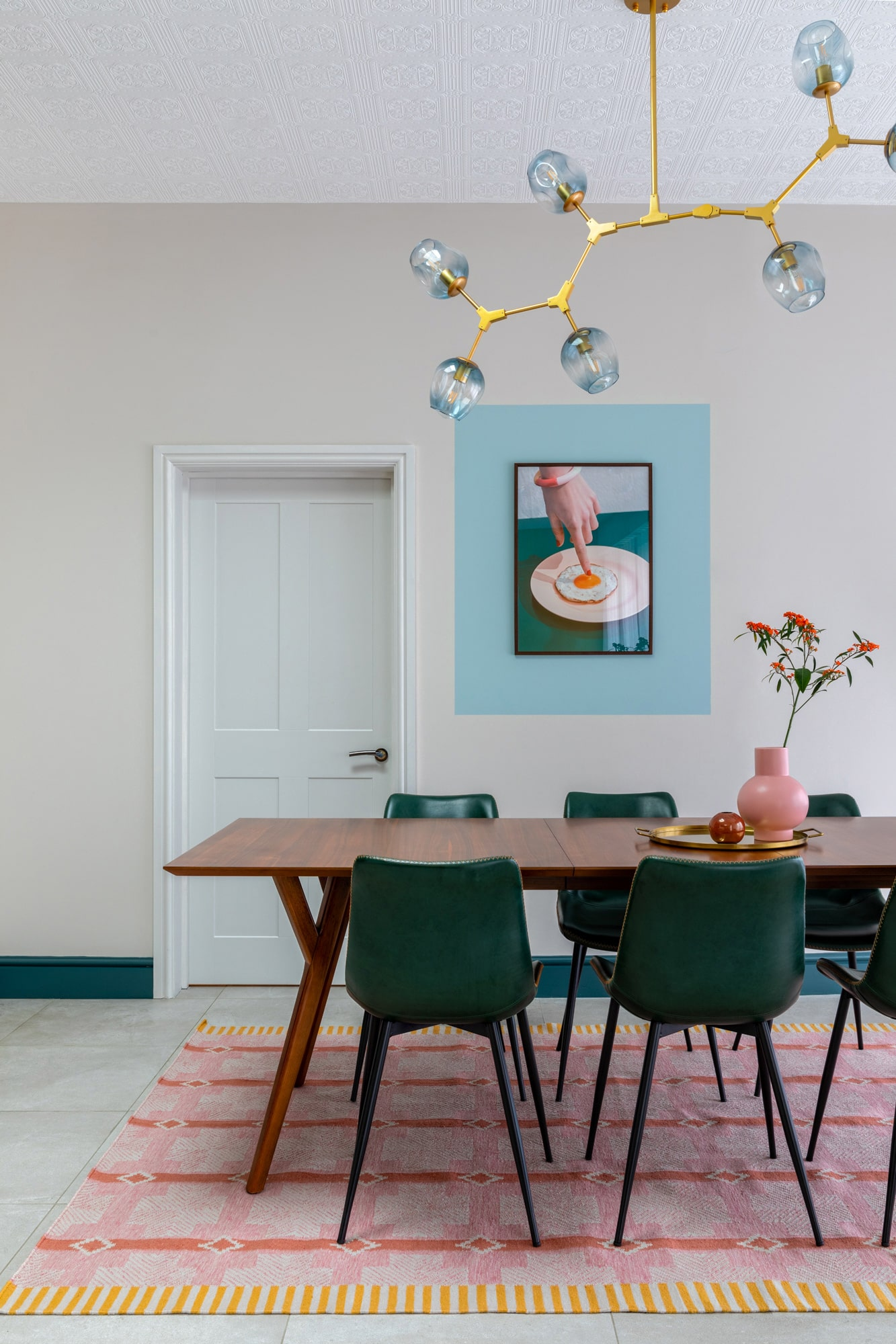 Interior photograph: a wooden dinning table, three green chairs, a round tray with pink vase on the tray. A beautiful poster on the wall with a female hand pointing on a fried egg on a plate in a blue frame.