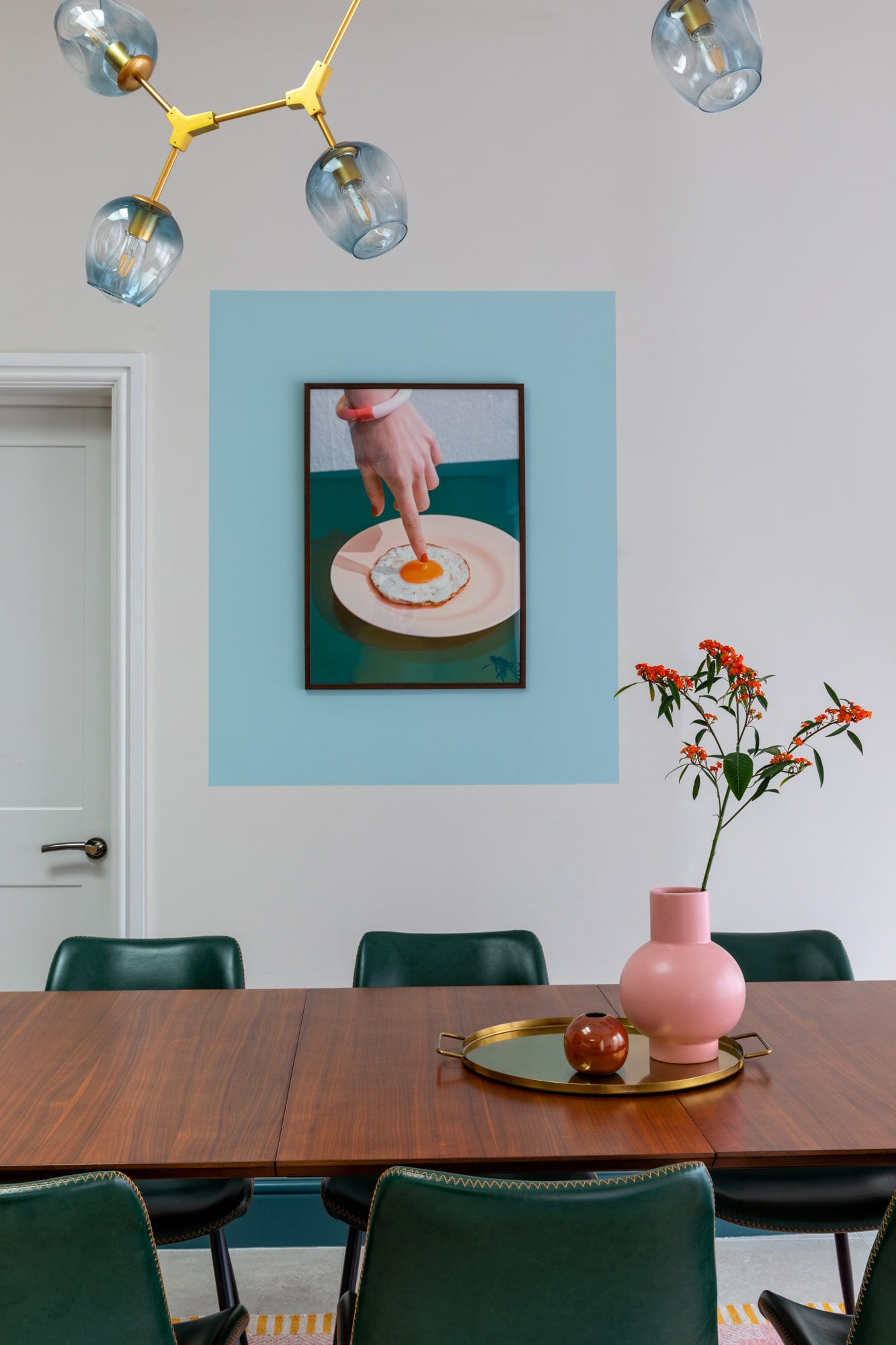 Interior photograph: a detail shot of a  wooden dinning table, three green chairs, a round tray with pink vase on the tray. A beautiful poster on the wall with a female hand pointing on a fried egg on a plate in a blue frame.
