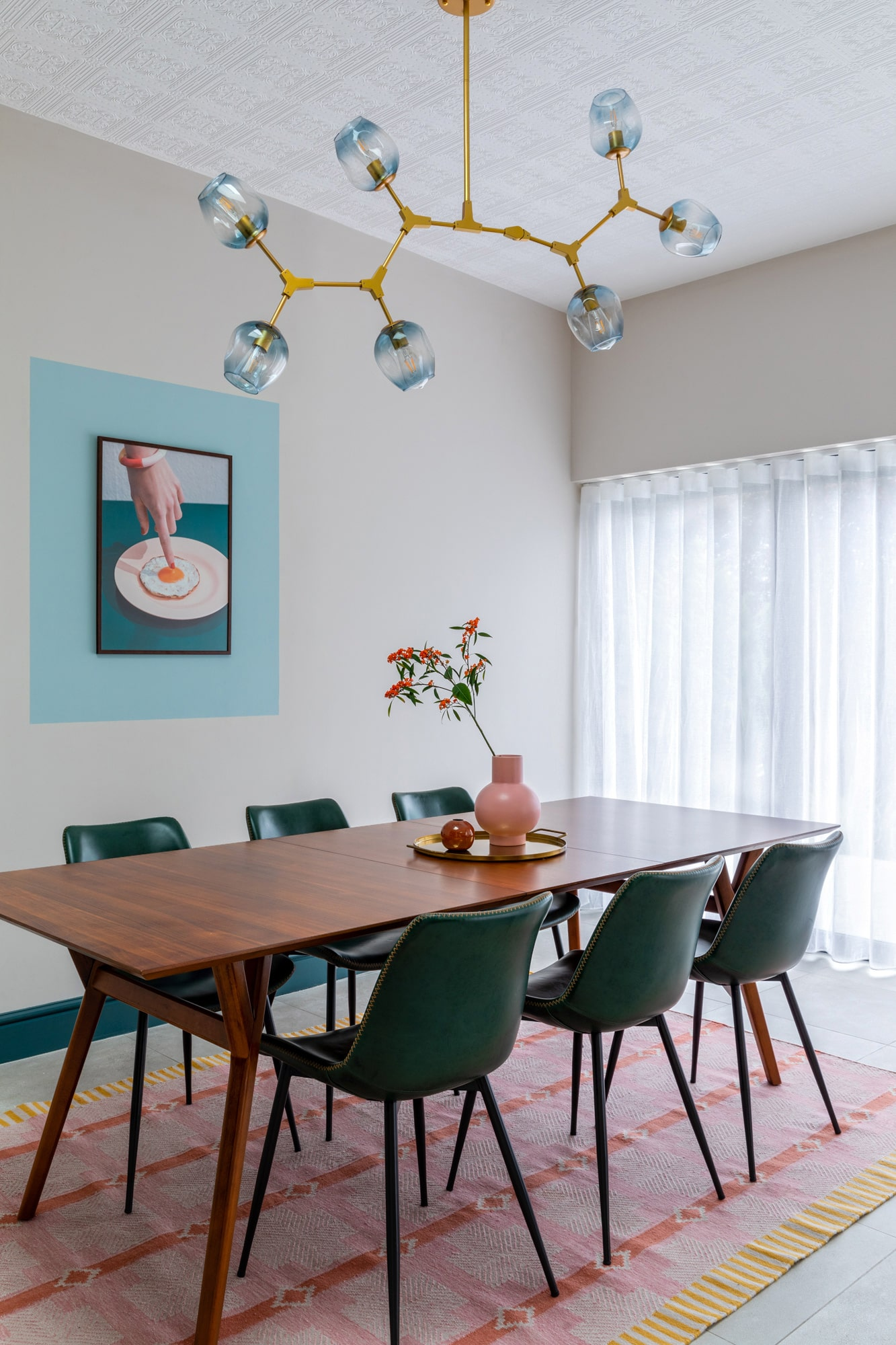 Interior photograph: a wooden dinning table, three green chairs, a round tray with pink vase on the tray. A beautiful poster on the wall with a female hand pointing on a fried egg on a plate in a blue paint frame.