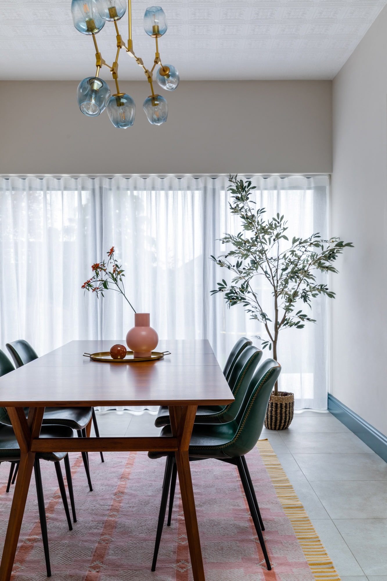 Interior photograph: a wooden dinning table in front of the window, three green chairs, a round tray with pink vase on the tray. A beautiful poster on the wall with a female hand pointing on a fried egg on a plate in a blue paint frame.