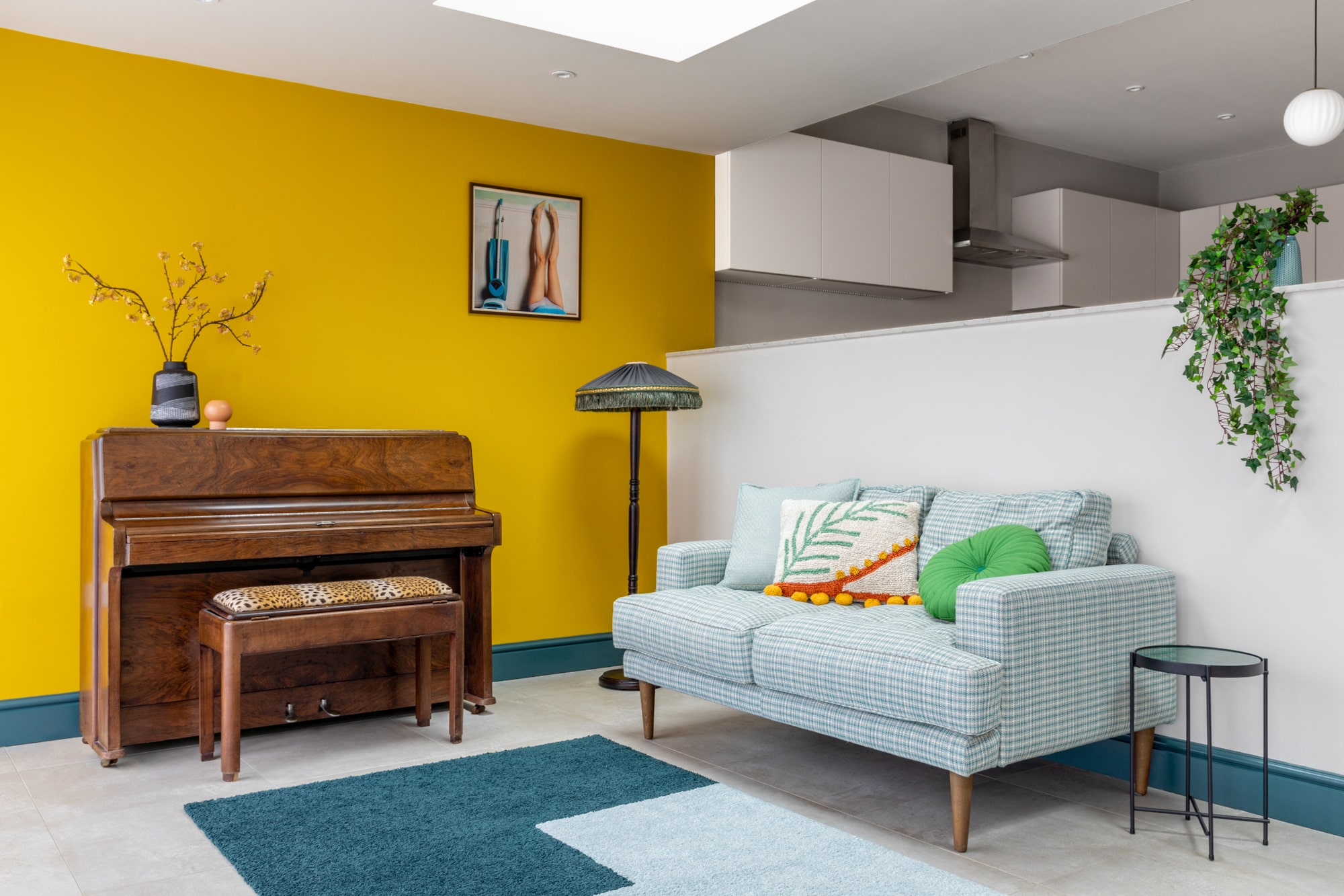 Interior design photo: a view from a dining area to a sitting living room area with a wooden table, a yellow wall, a brown piano and a sofa upholstered with green gingham pattern. There is a standing lamp on the left side of the sofa