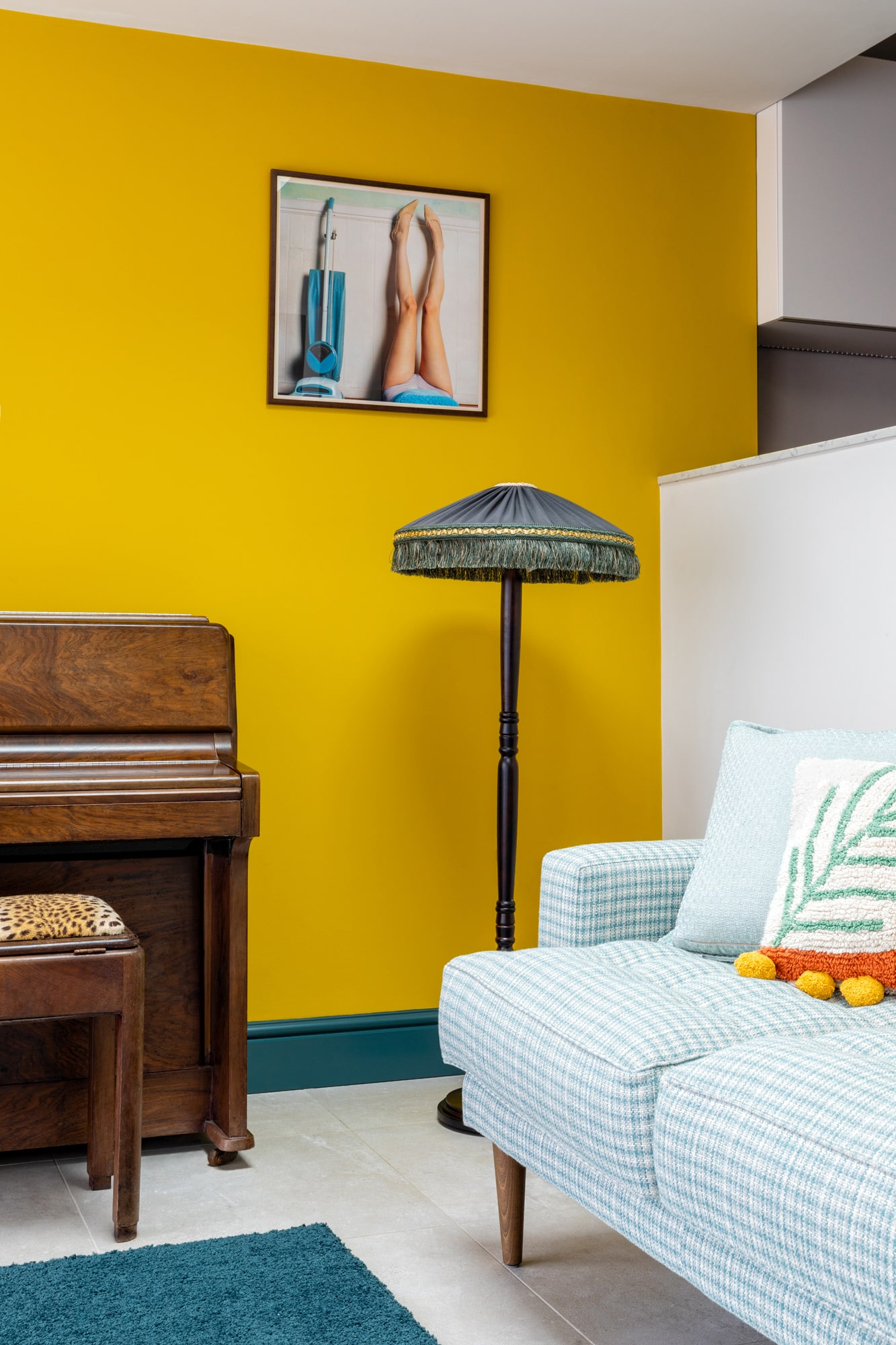 Interior design close up photo: a view from a dining area to a sitting living room area with a wooden table, a yellow wall, a brown piano and a sofa upholstered with green gingham pattern. There is a standing lamp on the left side of the sofa